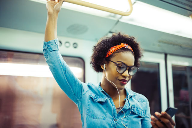 Smiling young African woman listening to music on the subway
