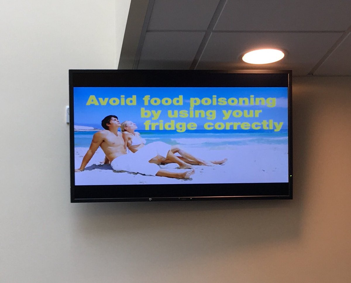 "TV screen showing a white couple on a sundrenched white beach with the text ""avoid food poisoning by using y our fridge correctly"""