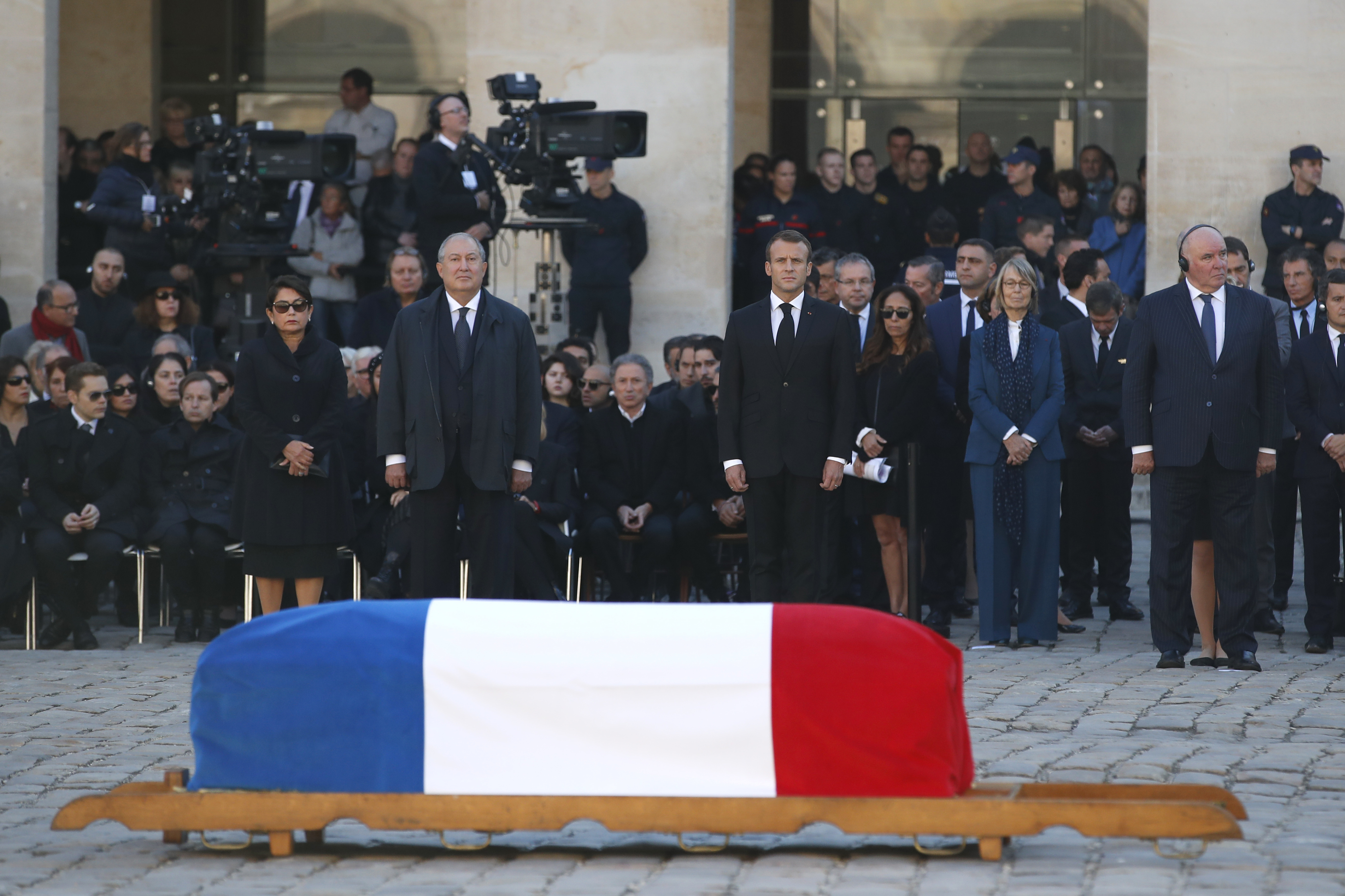French President Emmanuel Macron stands behind the coffin of Charles Aznavour
