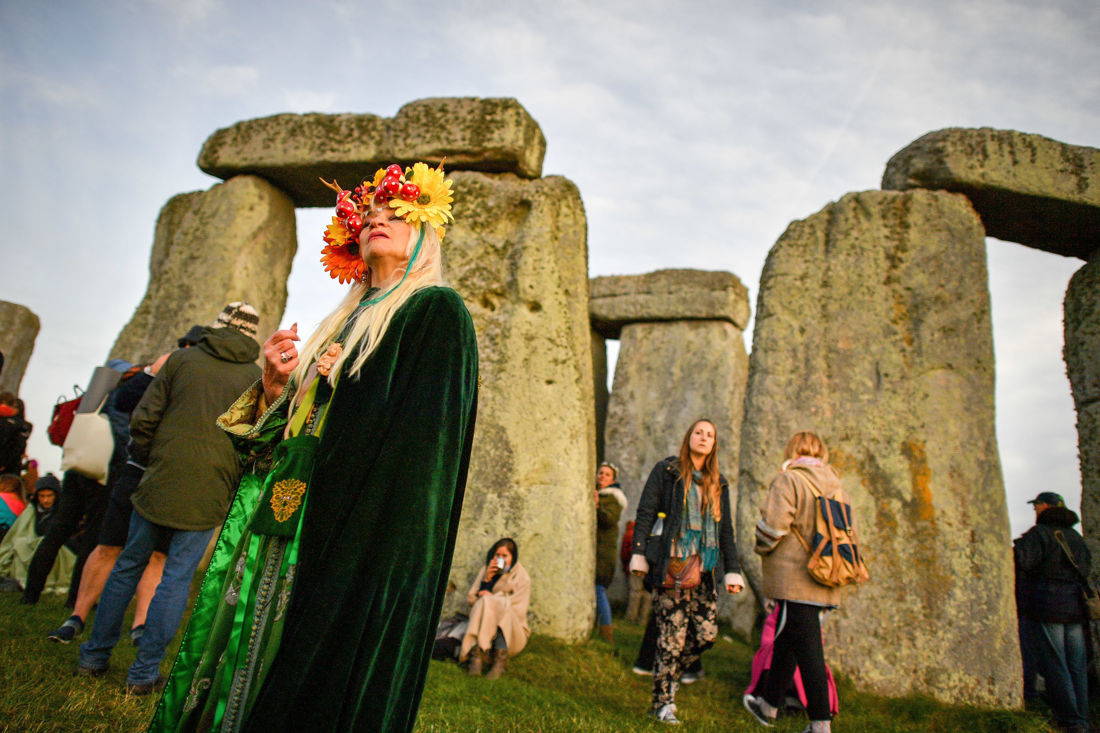 A woman wearing a colourful head-dress at Stonehenge during the 2018 Summer Solstice