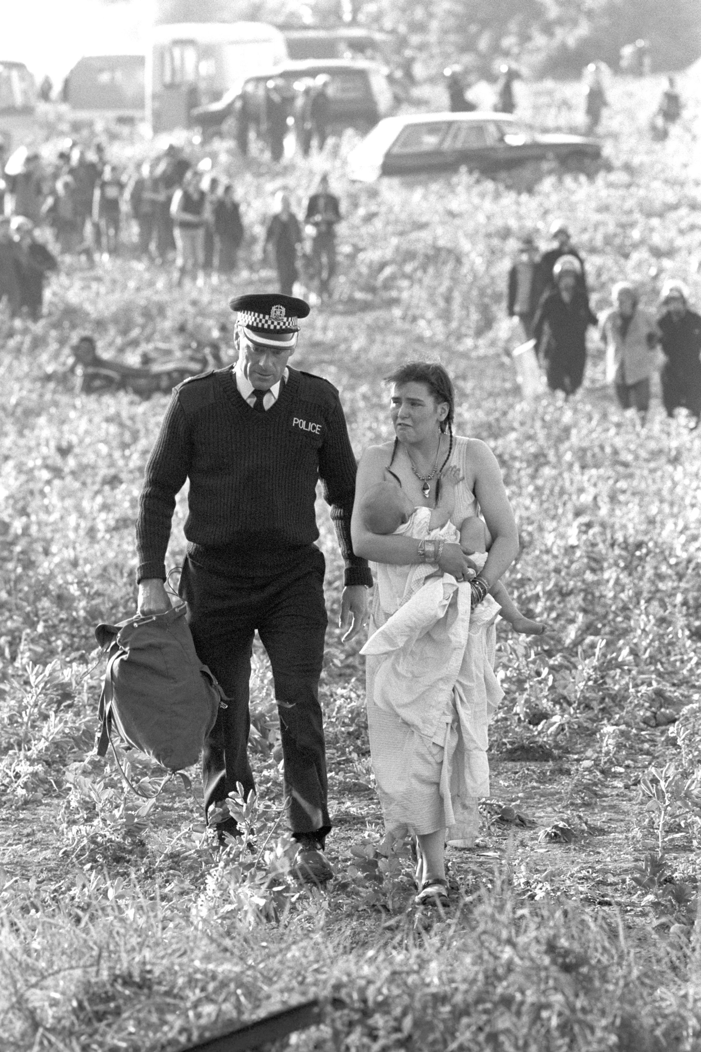 A woman holding a baby as she is led away by a policeman after violence erupted due to people attempting to hold a banned pop festival at Stonehenge in 1985