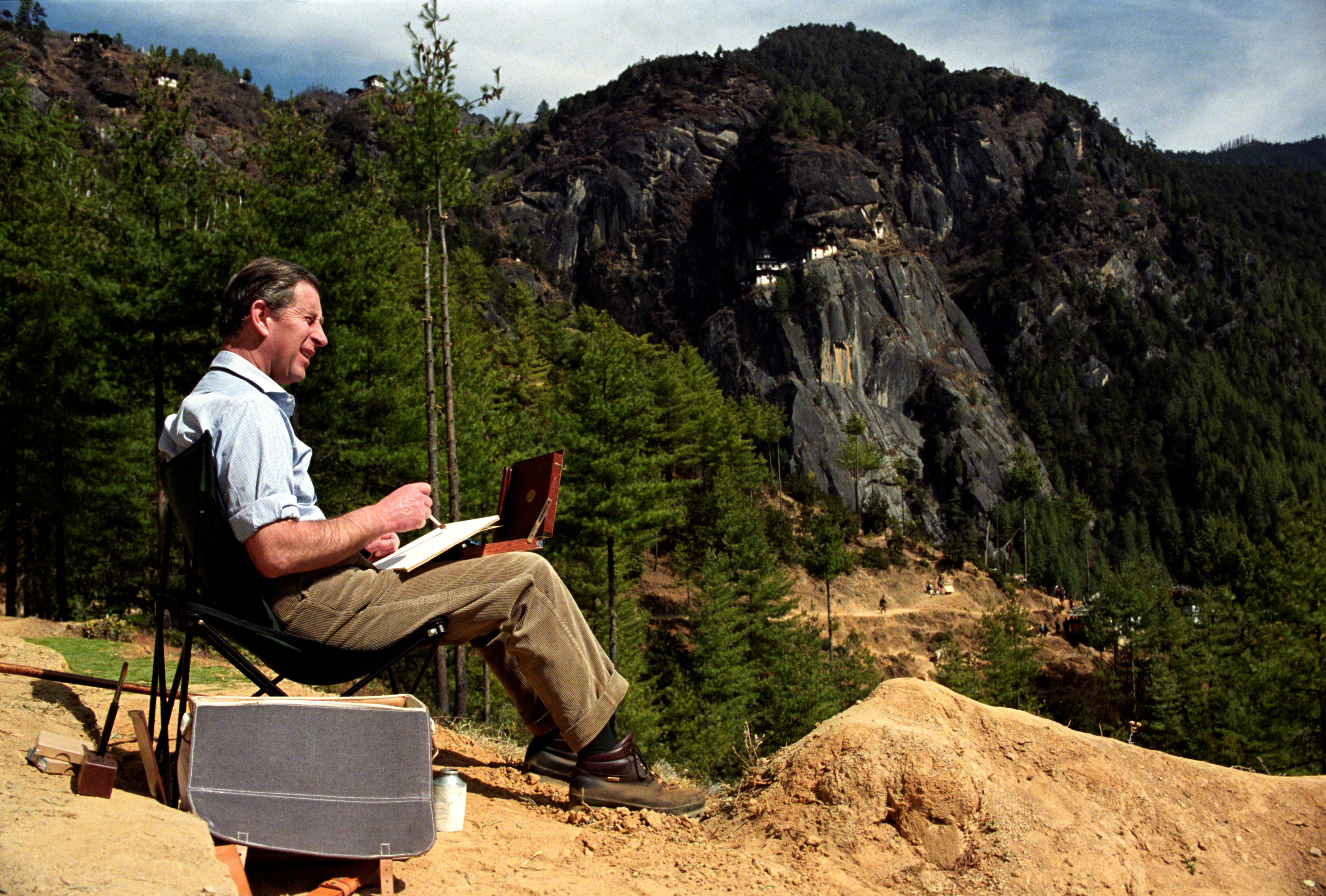 The Prince of Wales paints a water colour in the Bhutan Himalayas, while trekking up to the Tiger's Nest Monastery. (John Stillwell/PA)