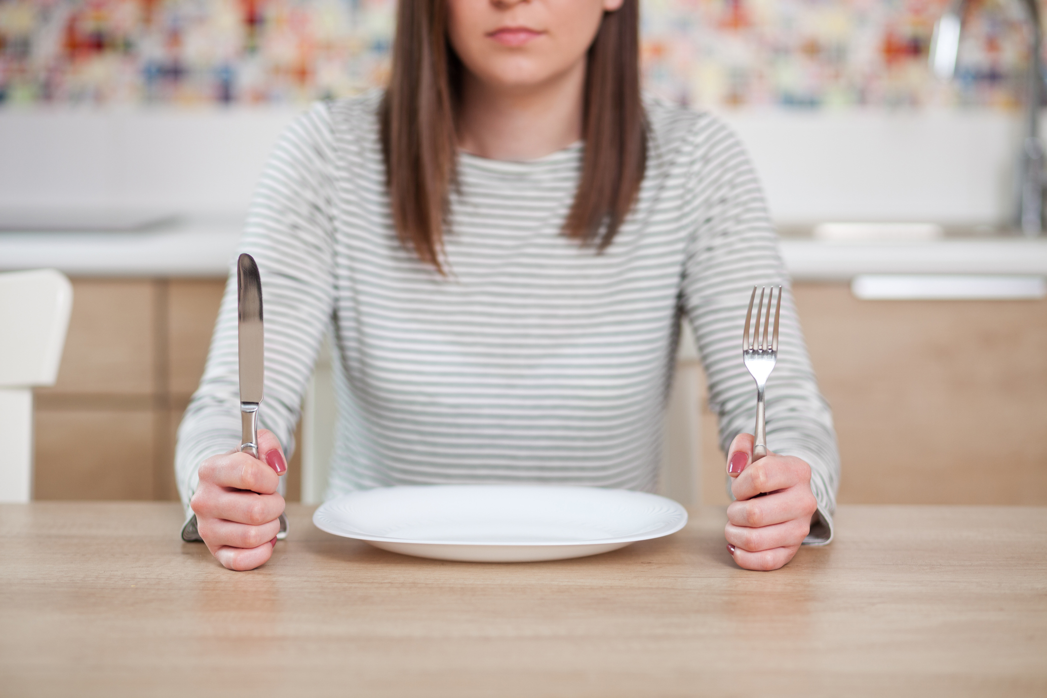 A woman in front of an empty plate