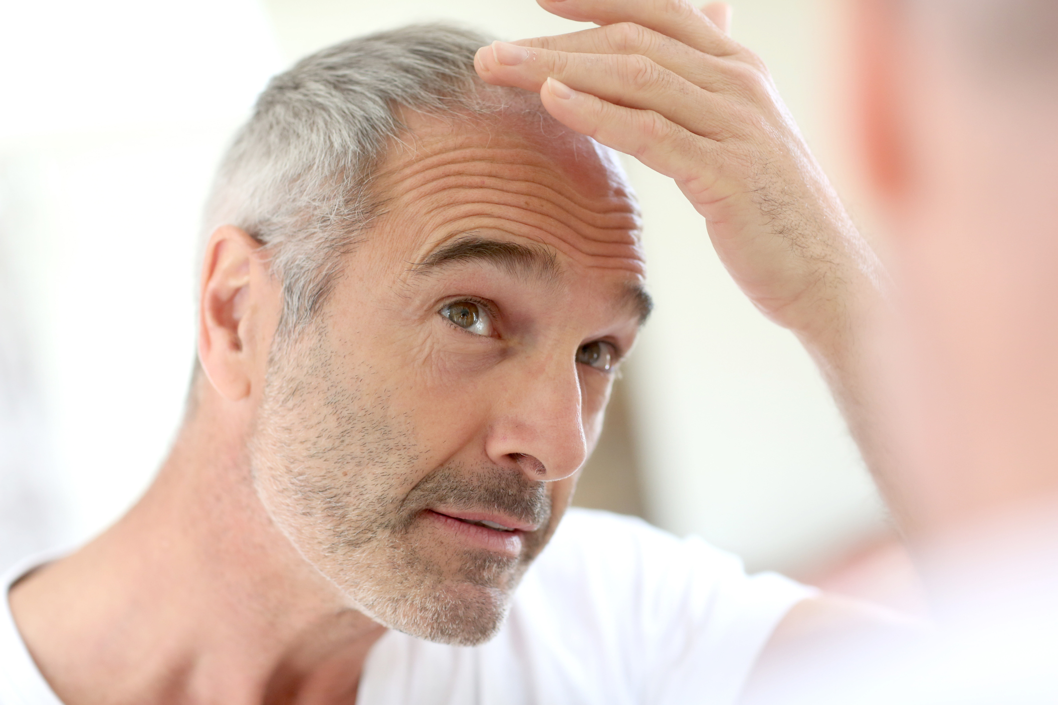 Mature man in bathroom taking care of his hair