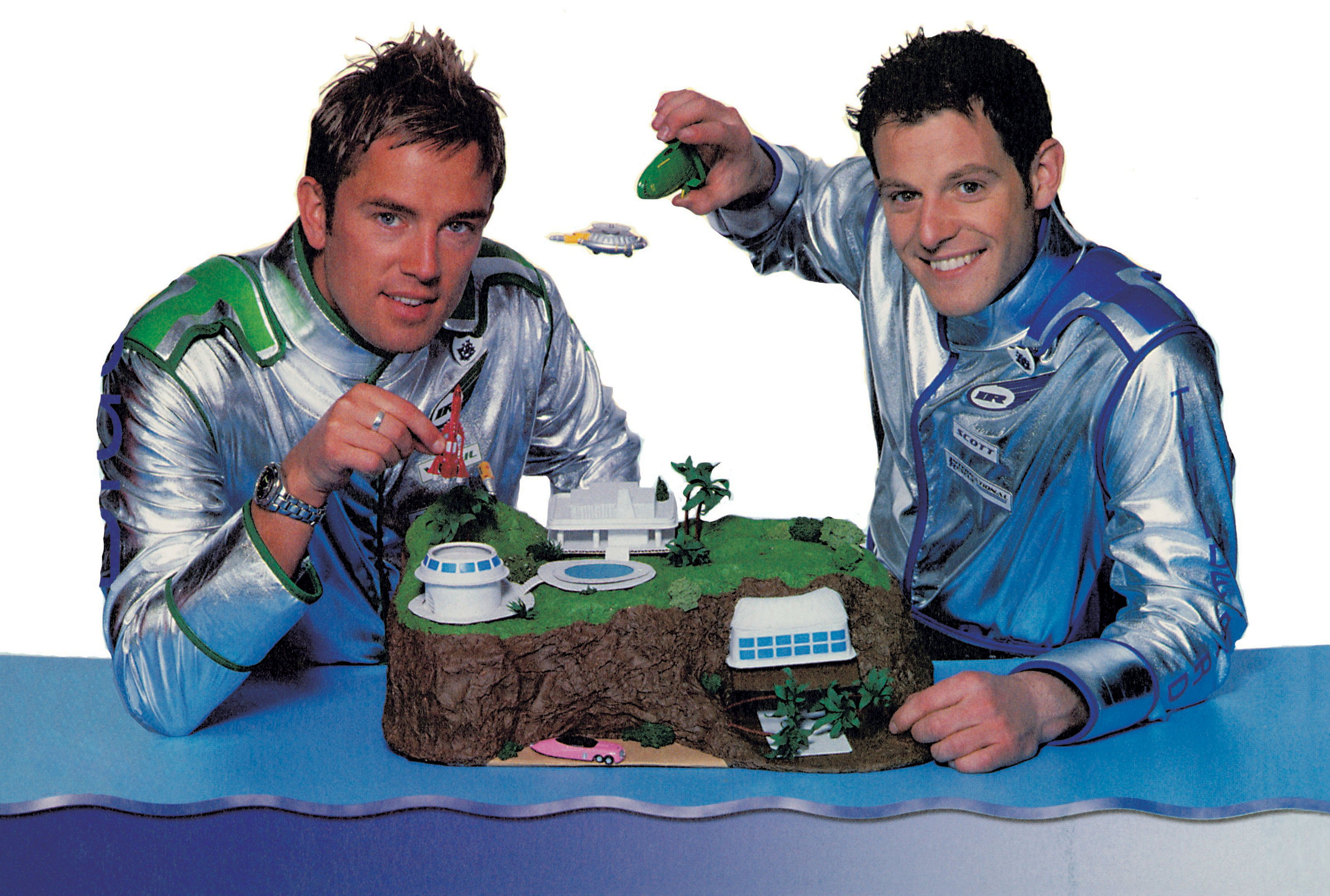 Two presenters play with a model of Tracy Island