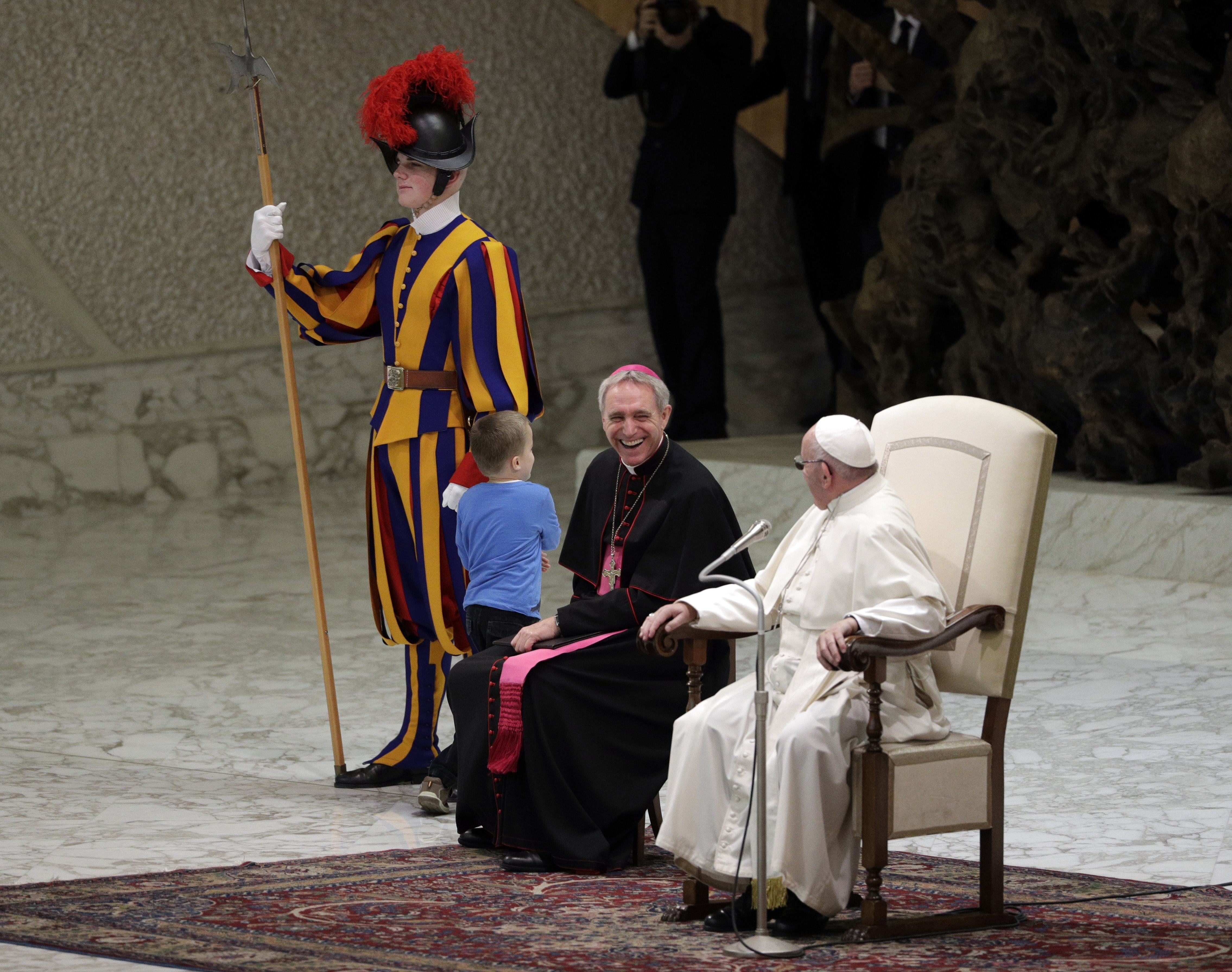 Pop Francis and Archbishop George Gaenswein laugh as the boy comes onstage