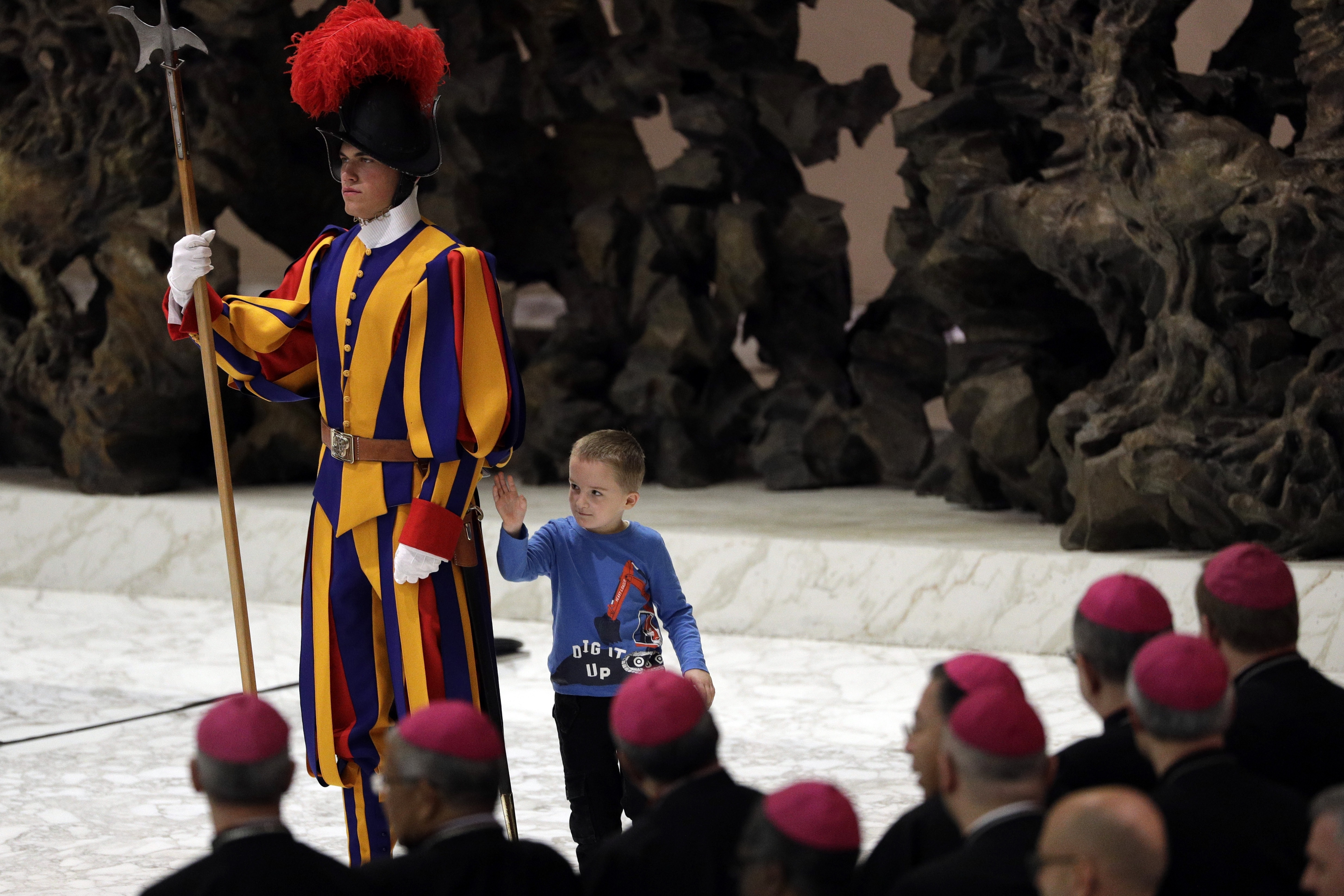 The child walks around the back of the guard