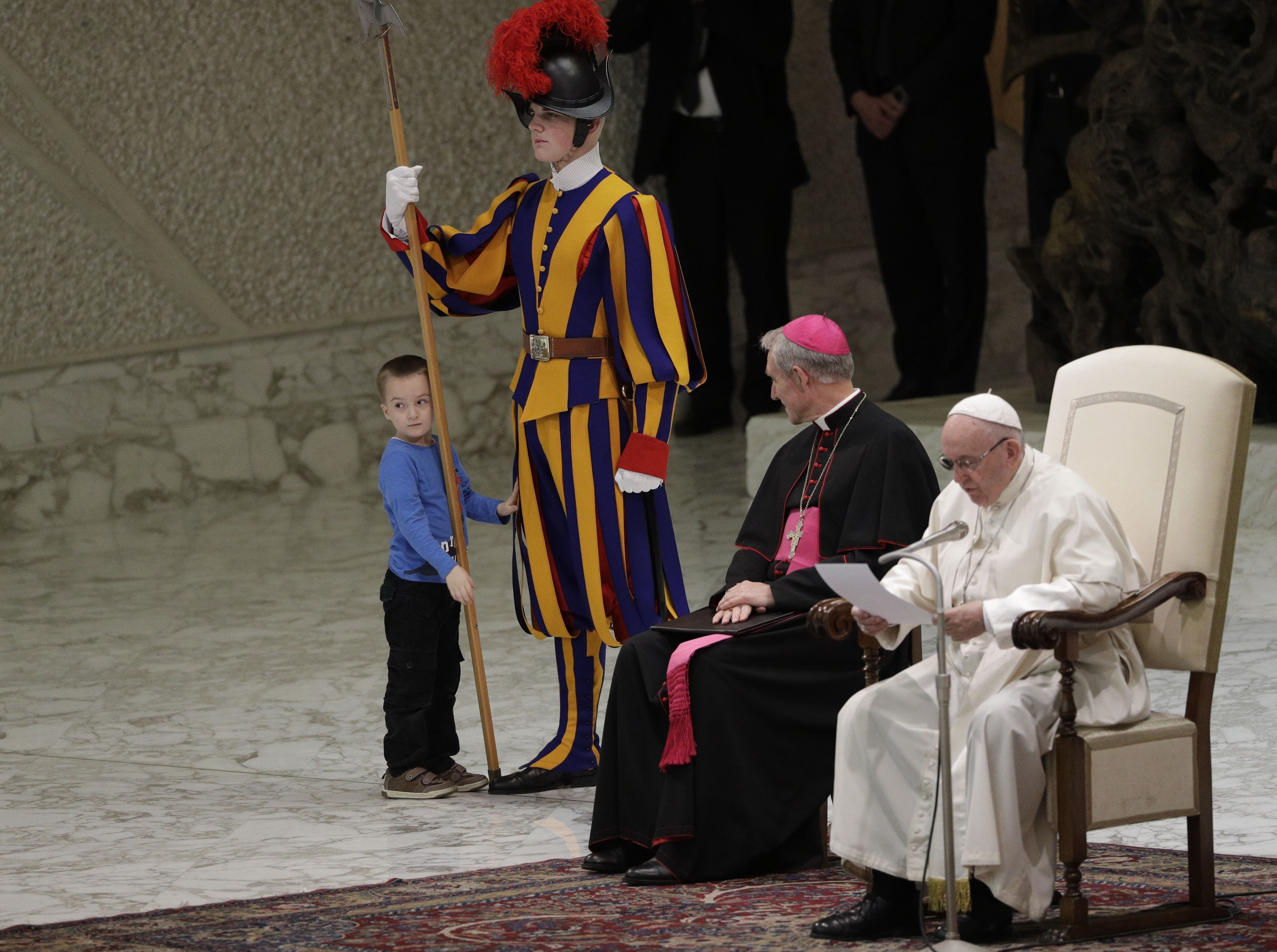 The child looks back at the audience in the Vatican hall