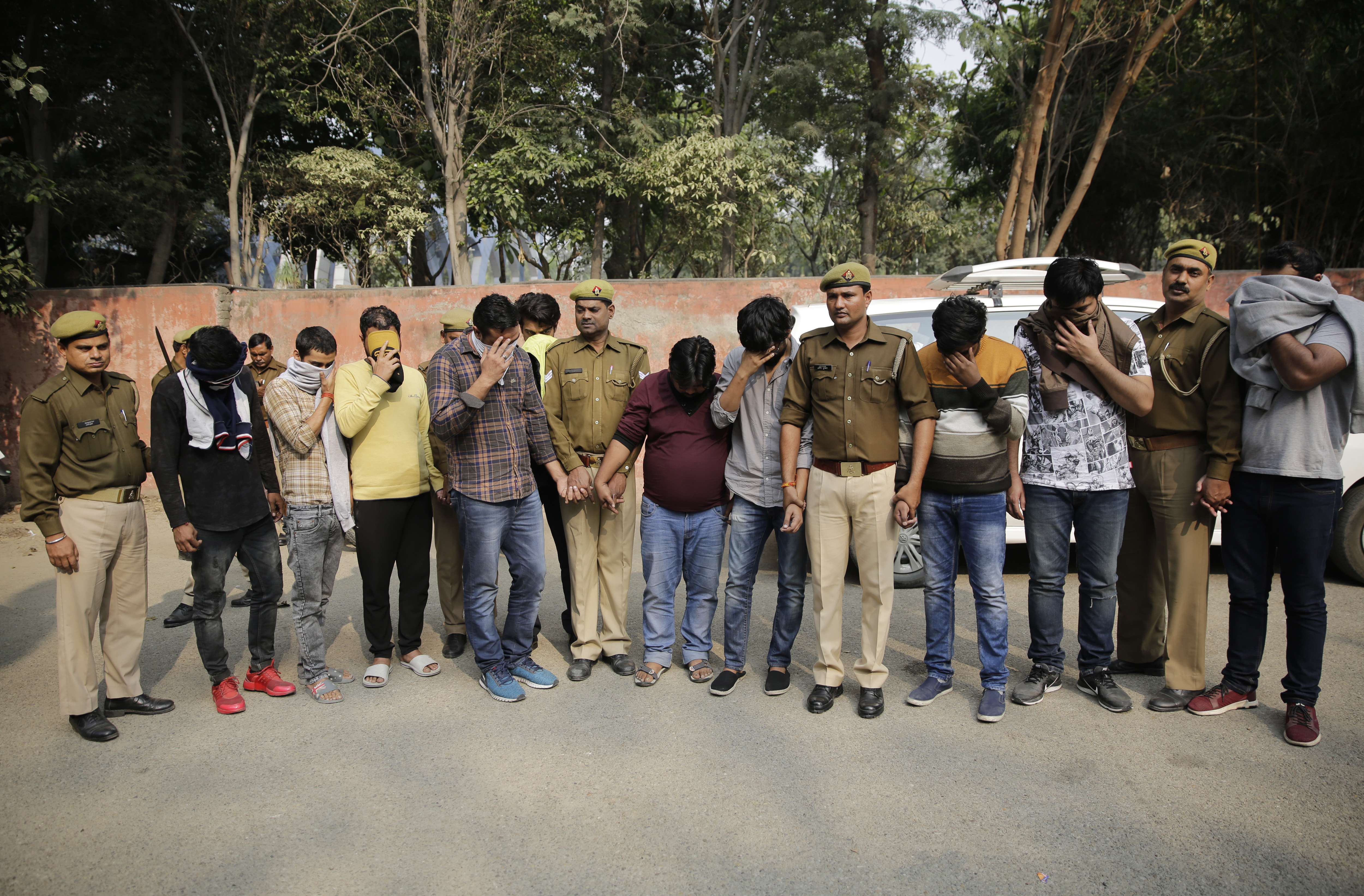 Alleged fraudsters are presented before media at a police station in Noida, a suburb of New Delhi