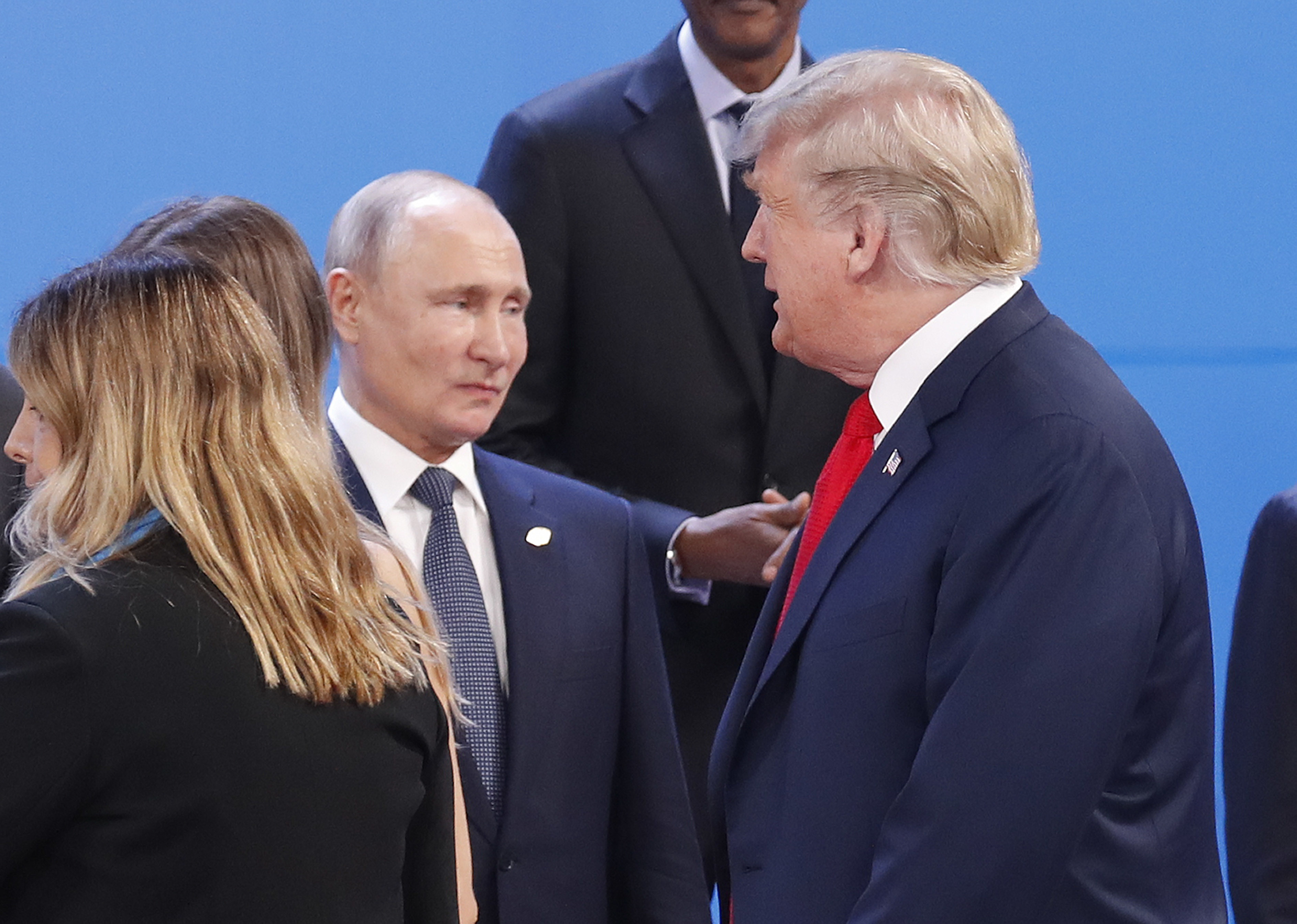 Donald Trump walks past Vladimir Putin as they gather for the group photo at the start of the G20 summit in Buenos Aires