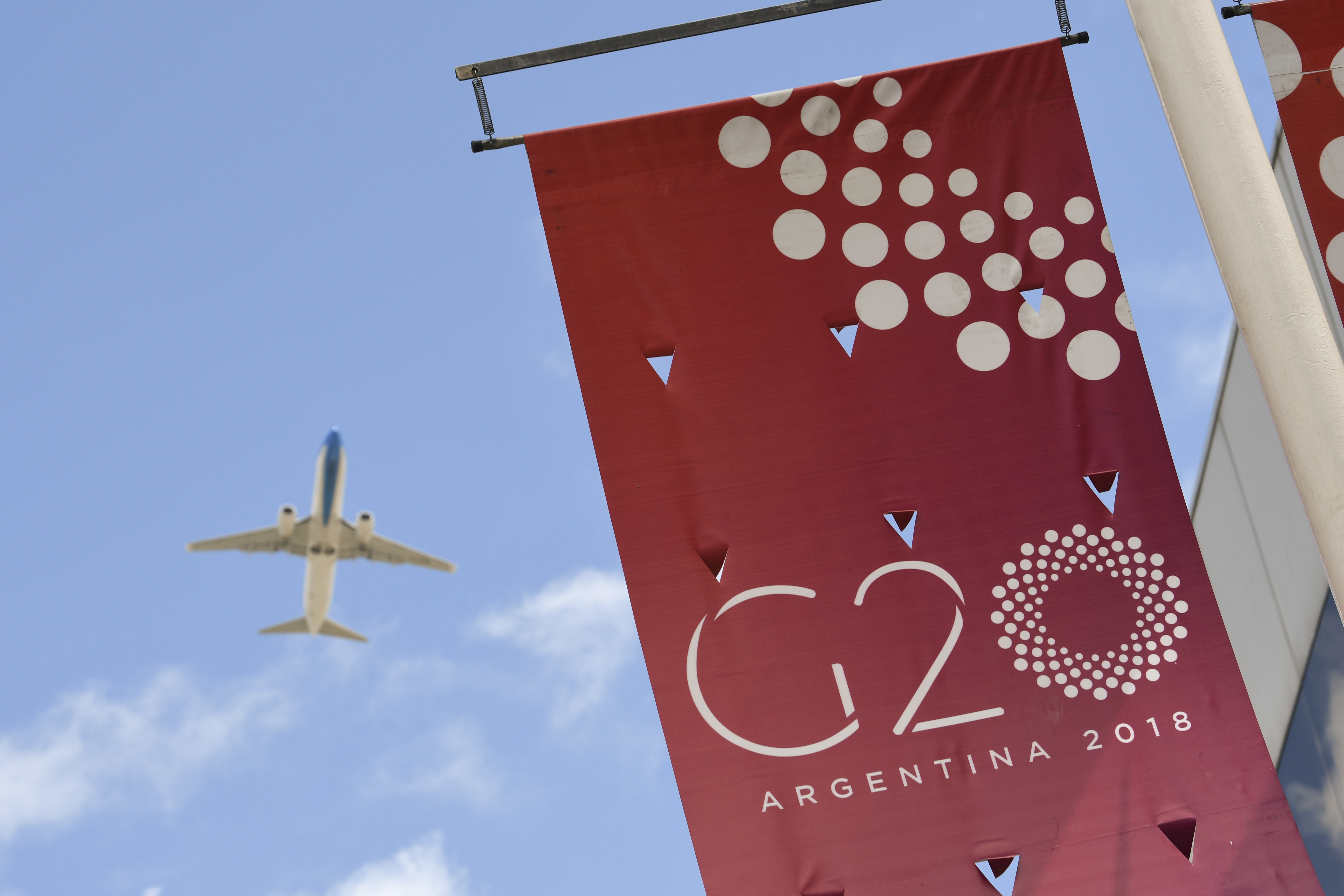A plane flies over the G20 summit venue at the Costa Salguero Centre in Buenos Aires, Argentina