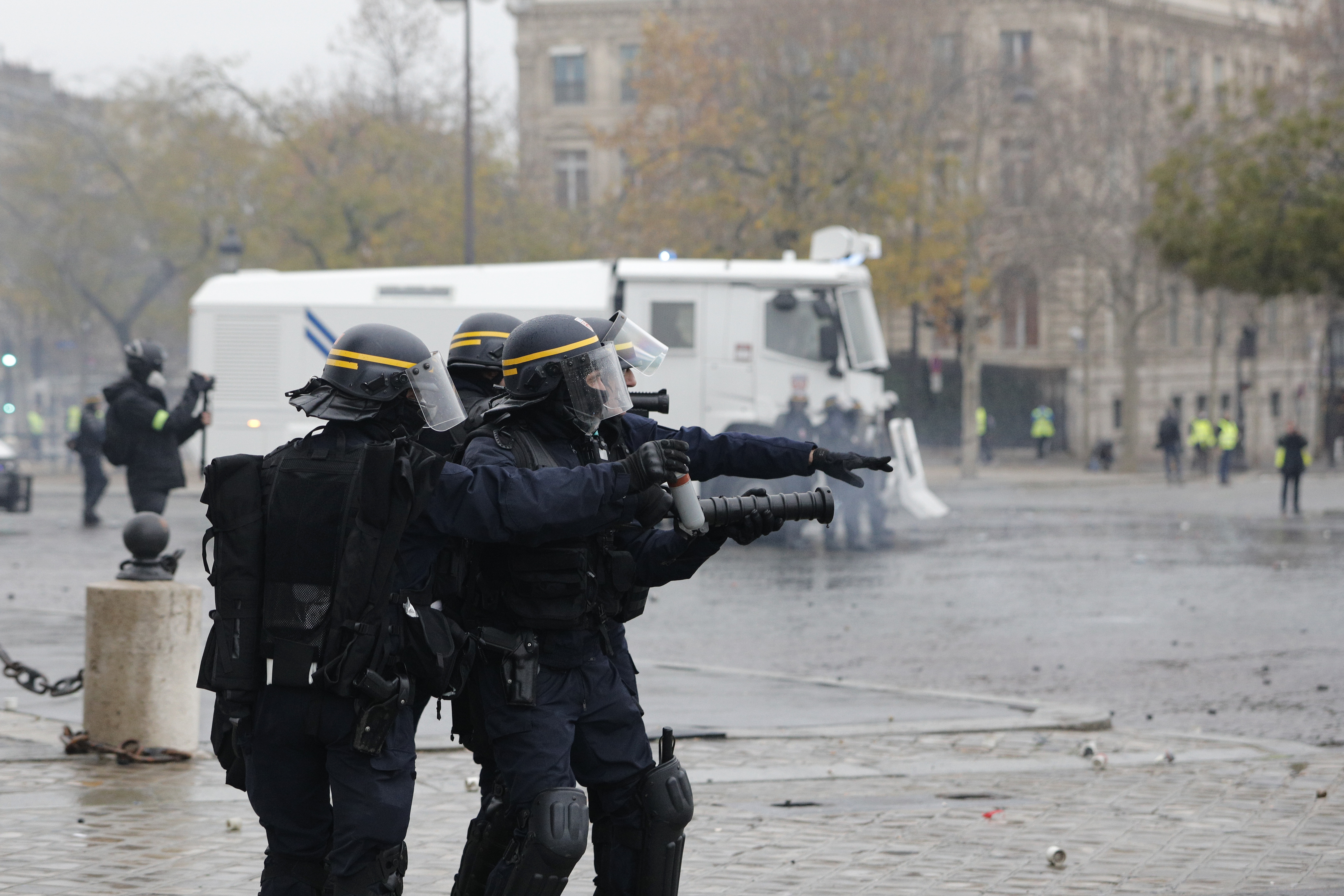 Riot police officers take up their position near the Arc de Triomphe during a demonstration