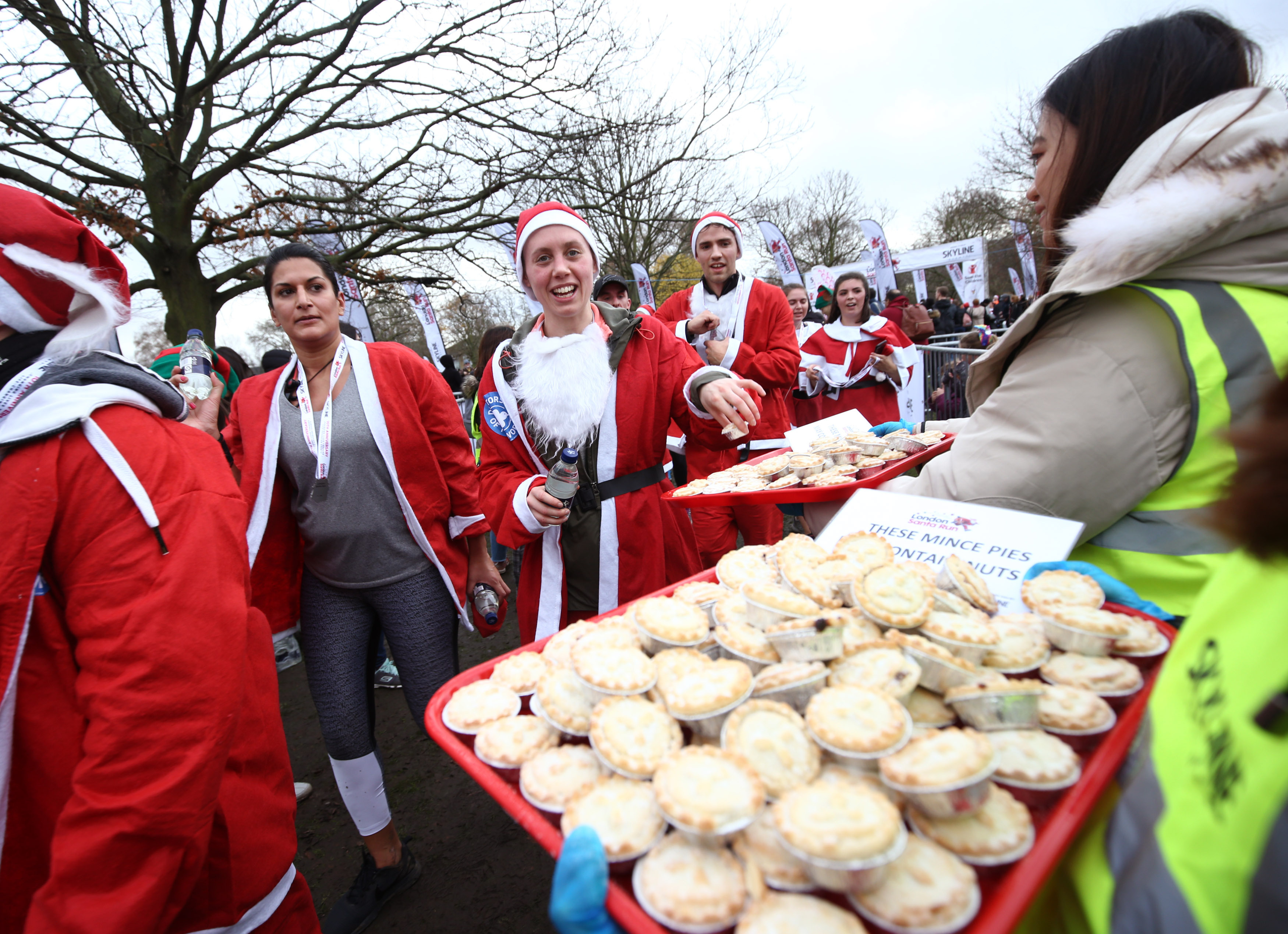 Participants take some mince pies after taking part in the London Santa Run, in Victoria Park, London