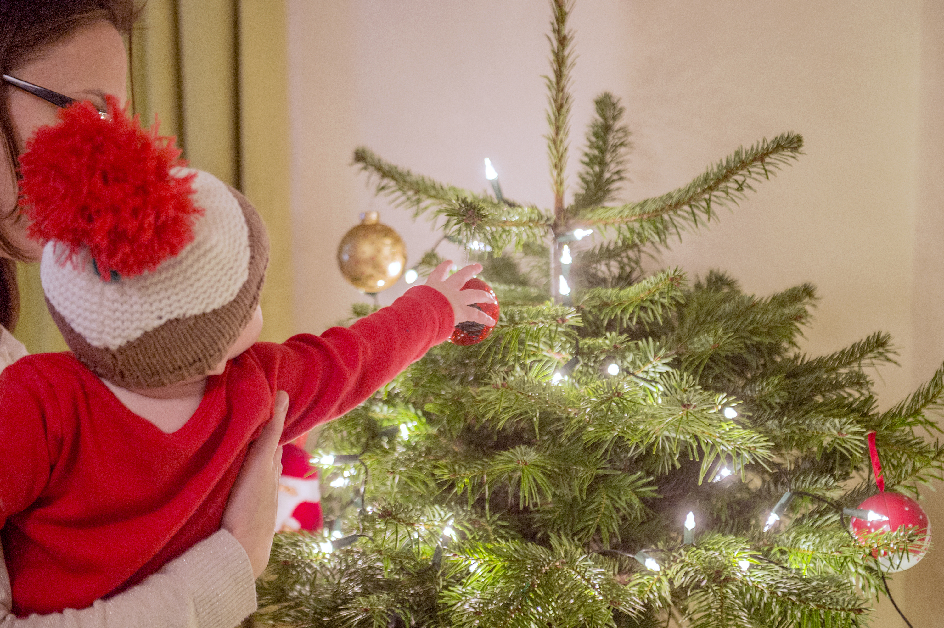 A young child touches a bauble on a Christmas tree