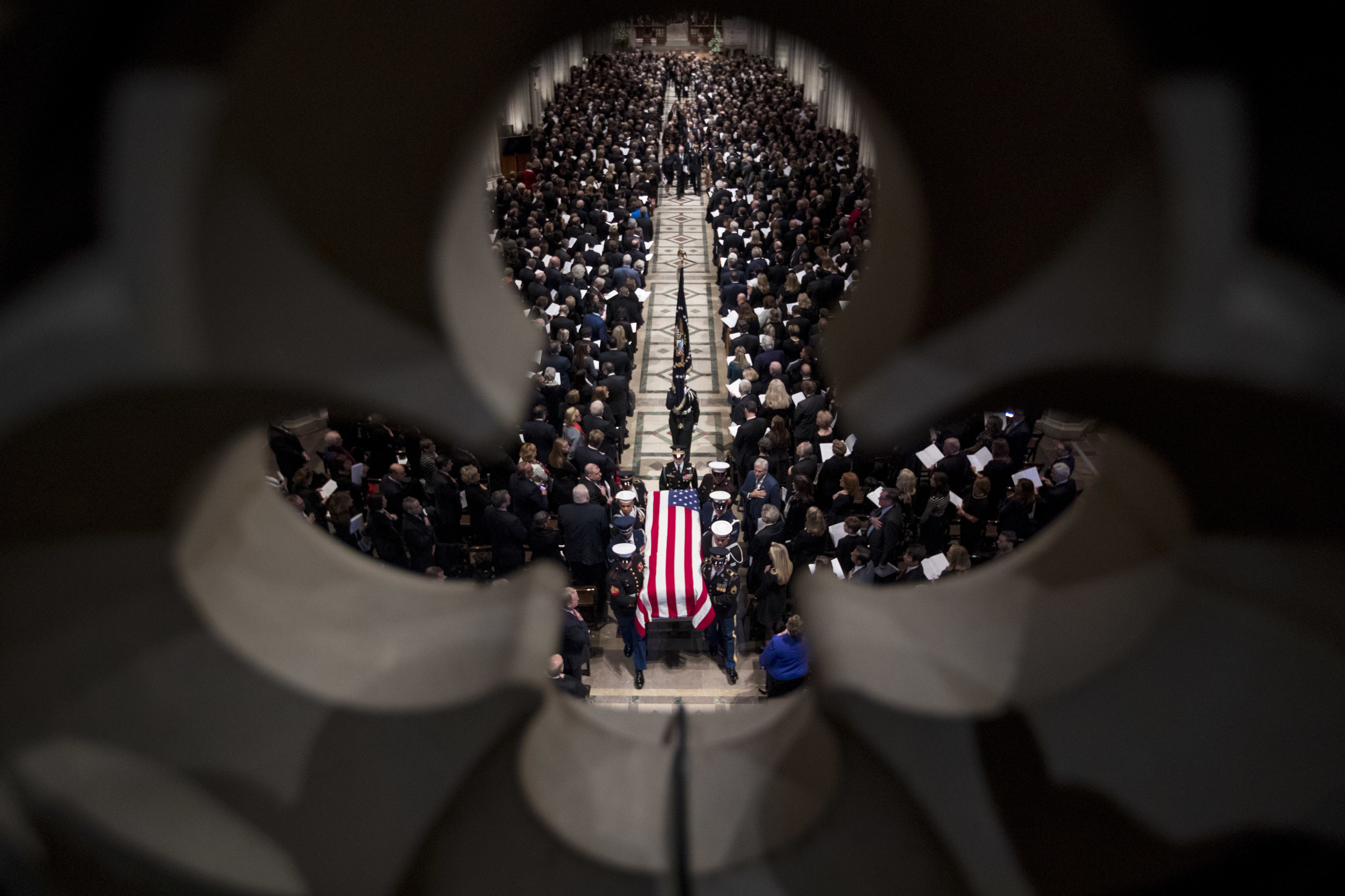 The flag-draped coffin of former president George HW Bush is carried out by a military honour guard