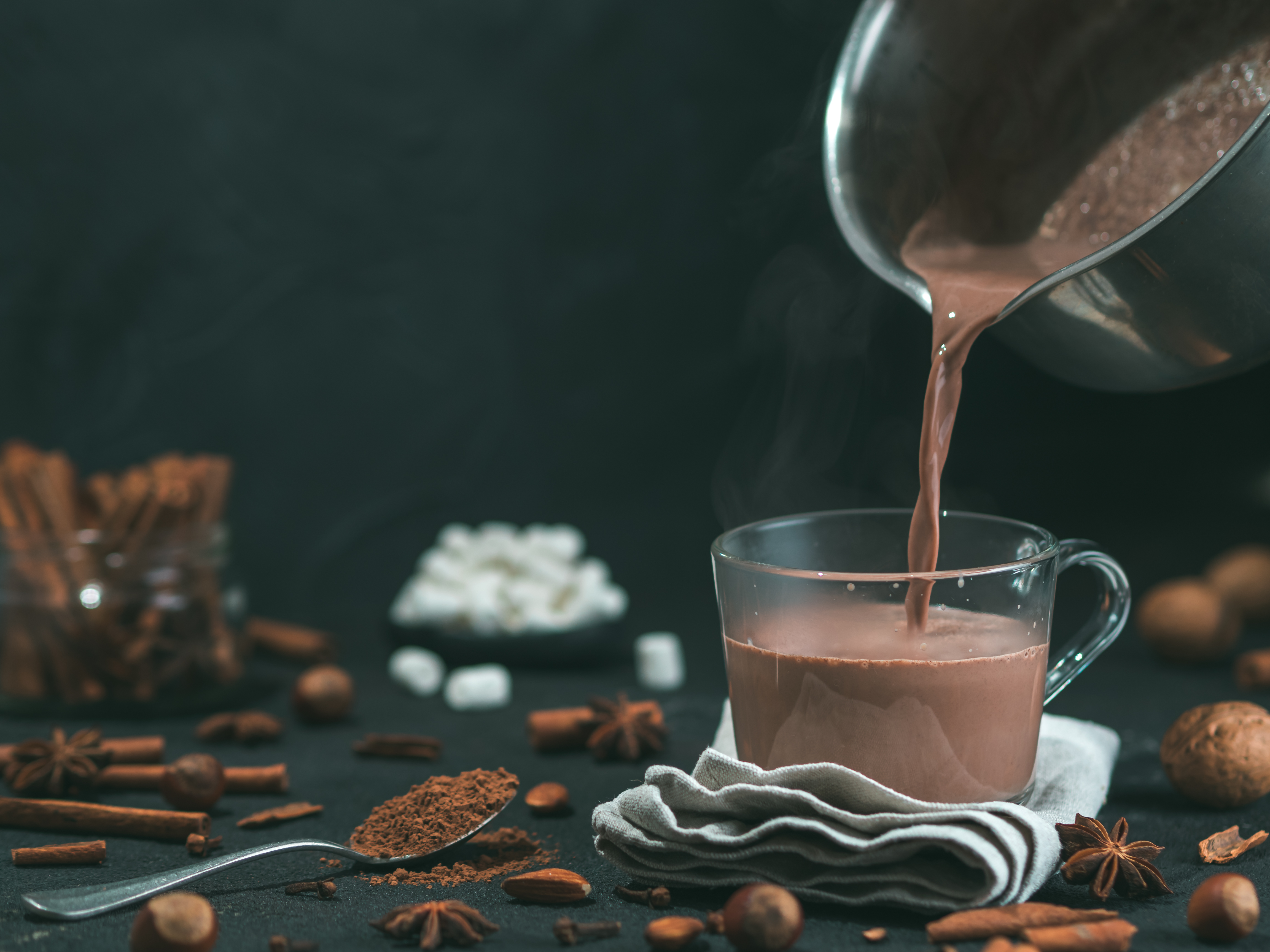 Pouring hot chocolate from a pan to a cup