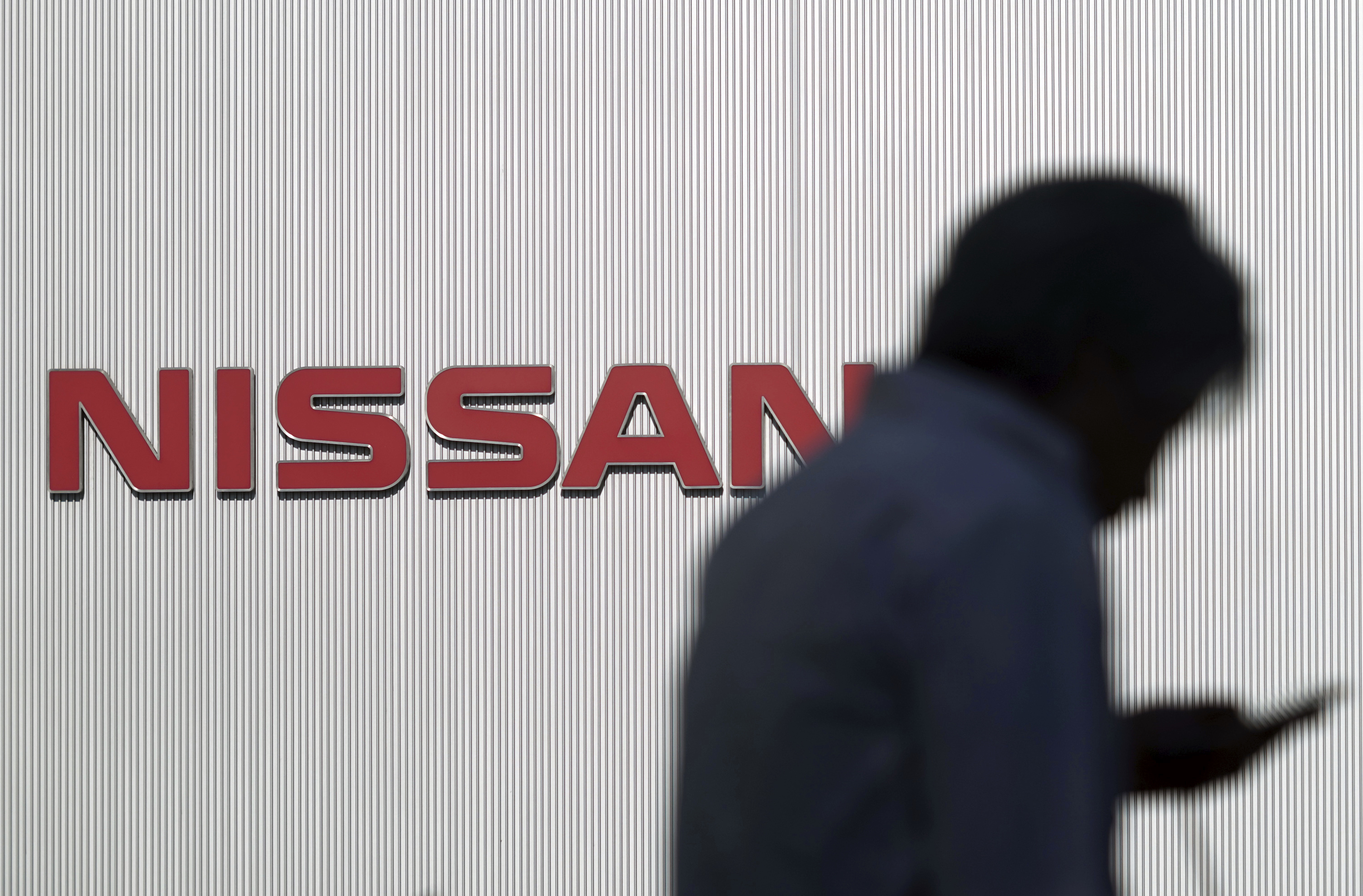 A man walks near the logo of Nissan its global headquarters in Yokohama, near Tokyo