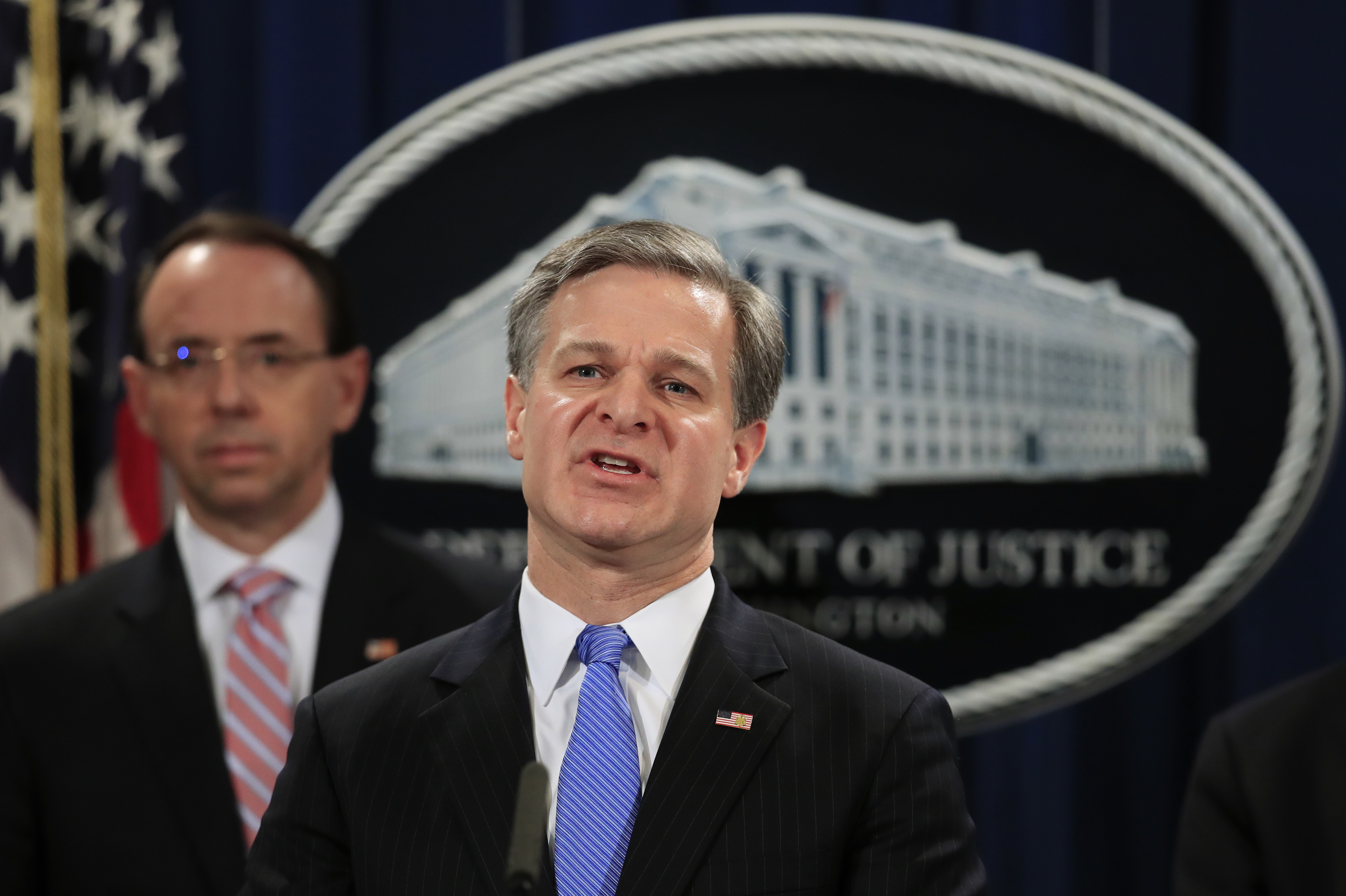 FBI director Christopher Wray with deputy attorney general Rod Rosenstein, speaks during a news conference at the Department of Justice in Washington