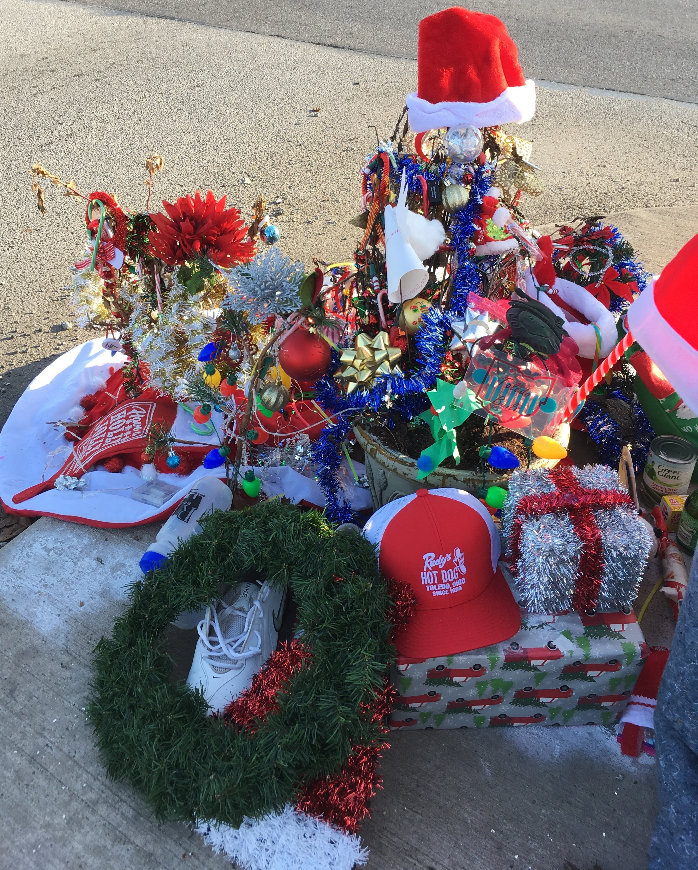 Christmas decorations and donations surround what is now known as the Christmas weed in Toledo, Ohio