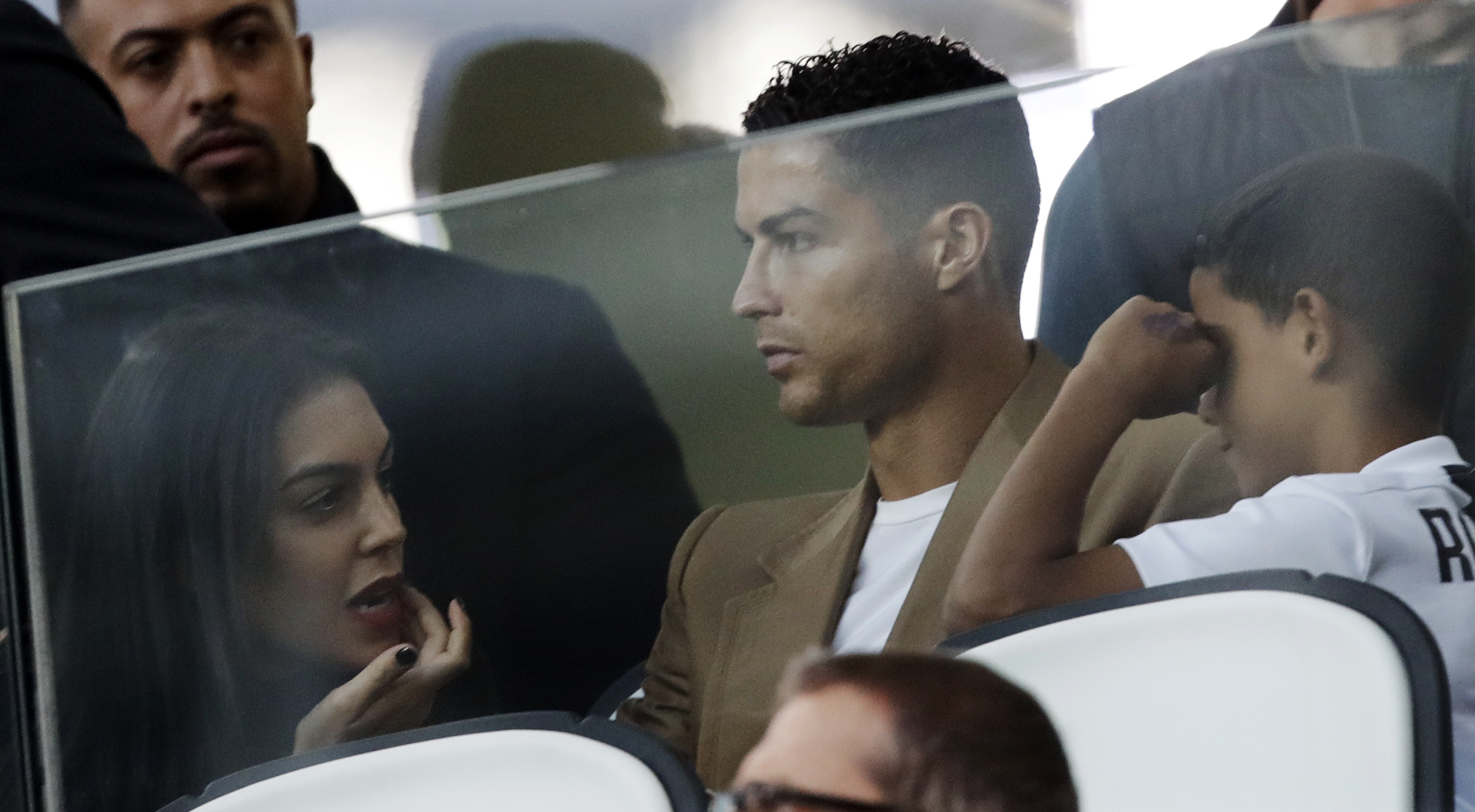 Cristiano Ronaldo is flanked by his girlfriend Georgina, left, and his son Cristiano Jr, as he sits in the stands during a Champions League group H soccer match between Juventus and Young Boys, at the Allianz stadium in Turin