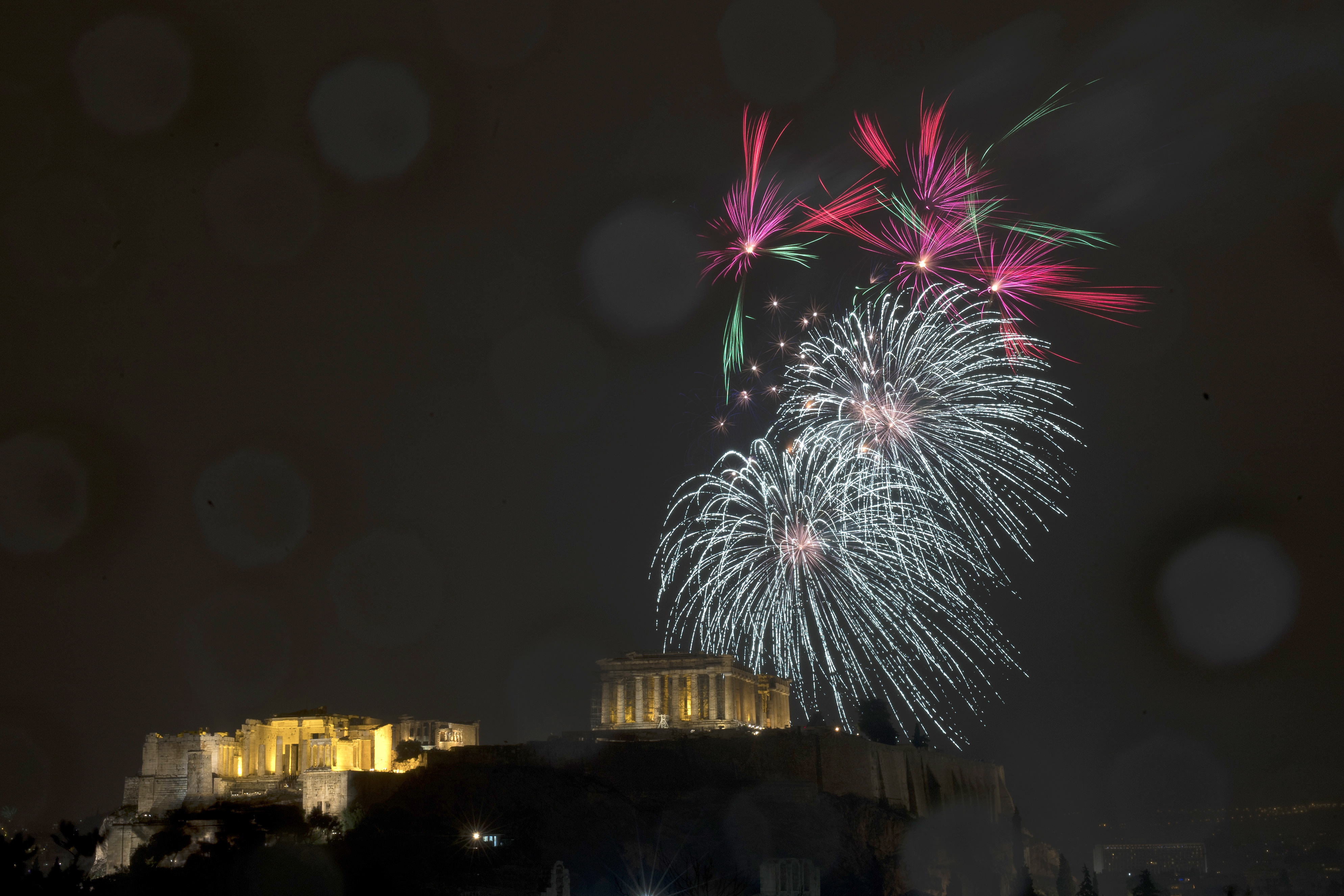 Fireworks explode over the ancient Parthenon temple at the Acropolis hill for the the New Year's Eve celebrations during a rainfall in Athens