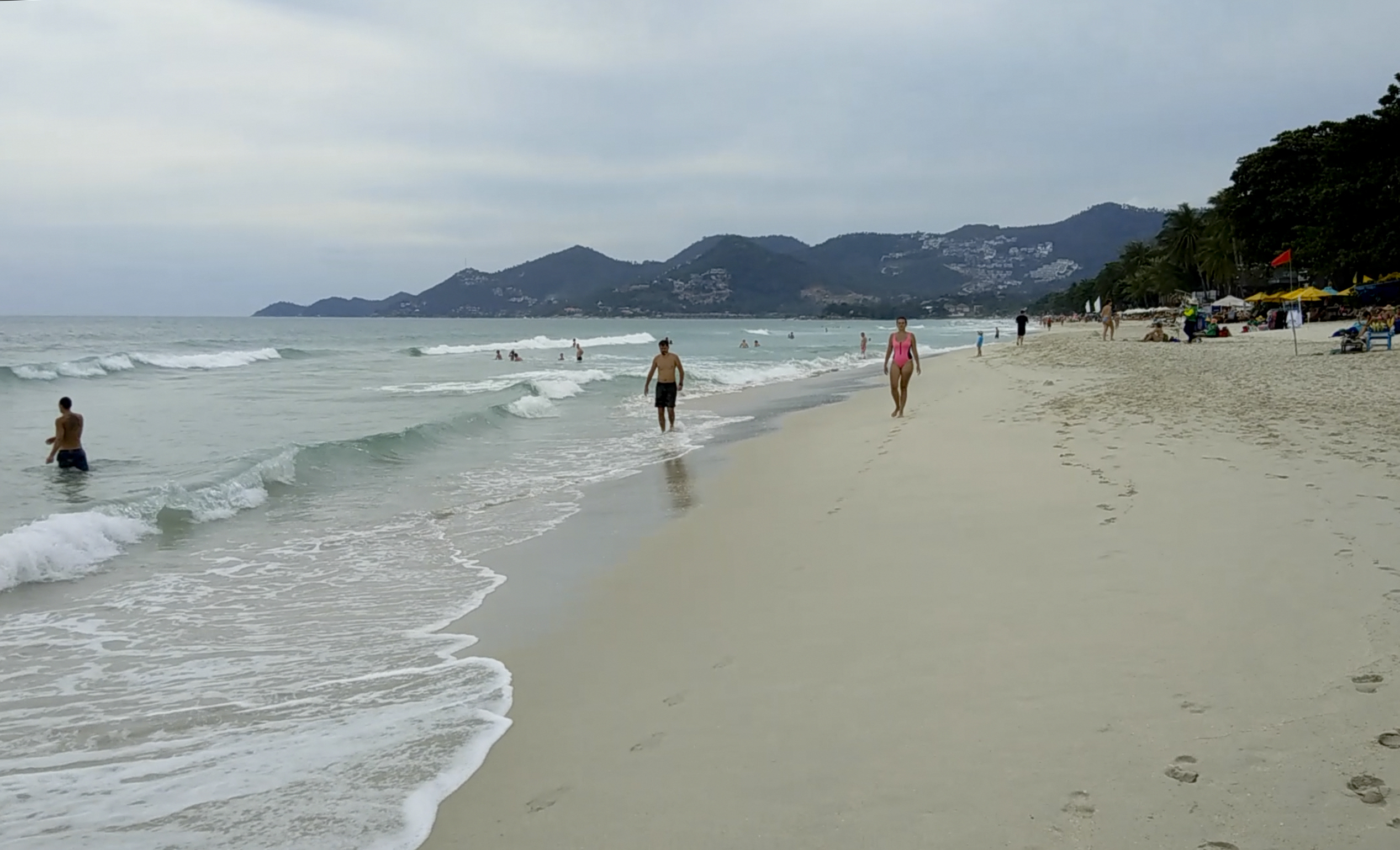 Tourists walk in Chaweng Beach in Koh Samui, Thailand as a red flag indicating expected rough weather conditions displayed on the beach