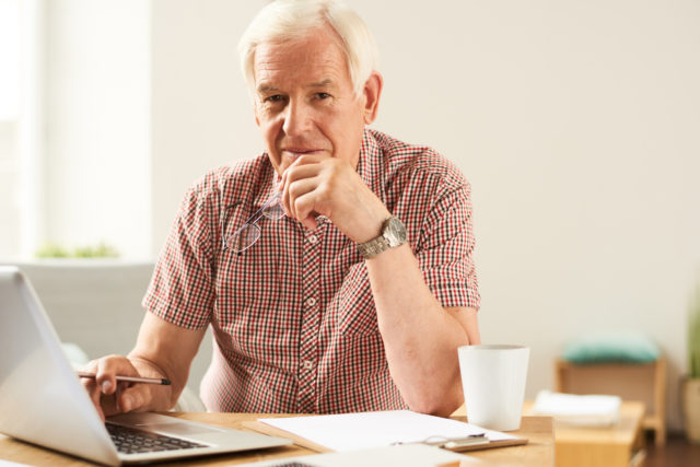 Portrait of modern senior man using laptop at home working and looking at camera, smiling