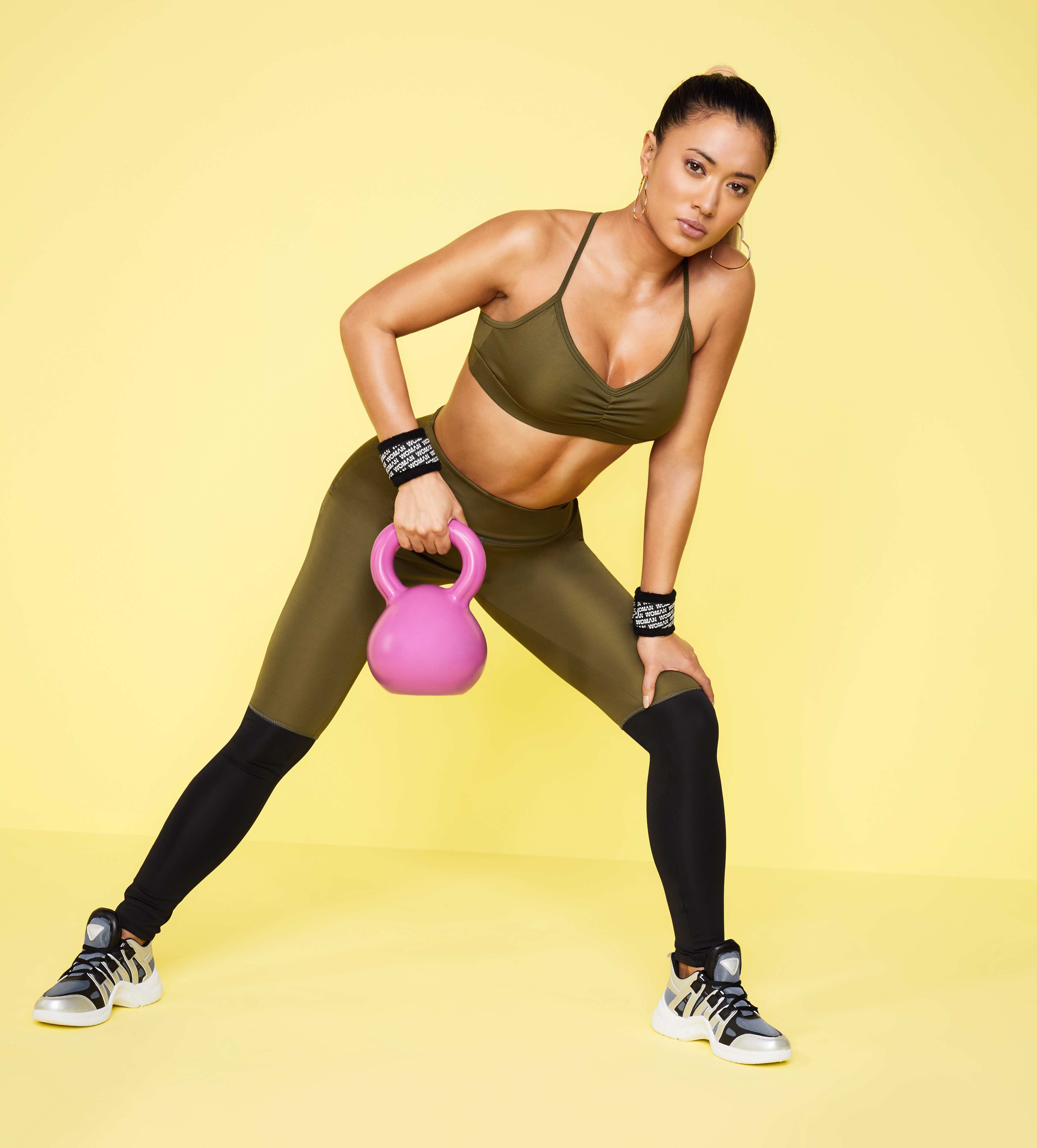 model wearing Boohoo Fit Premium Back Strap Detail Bra; Fit Premium Colourblock Leggings; Chunky Dad Trainers