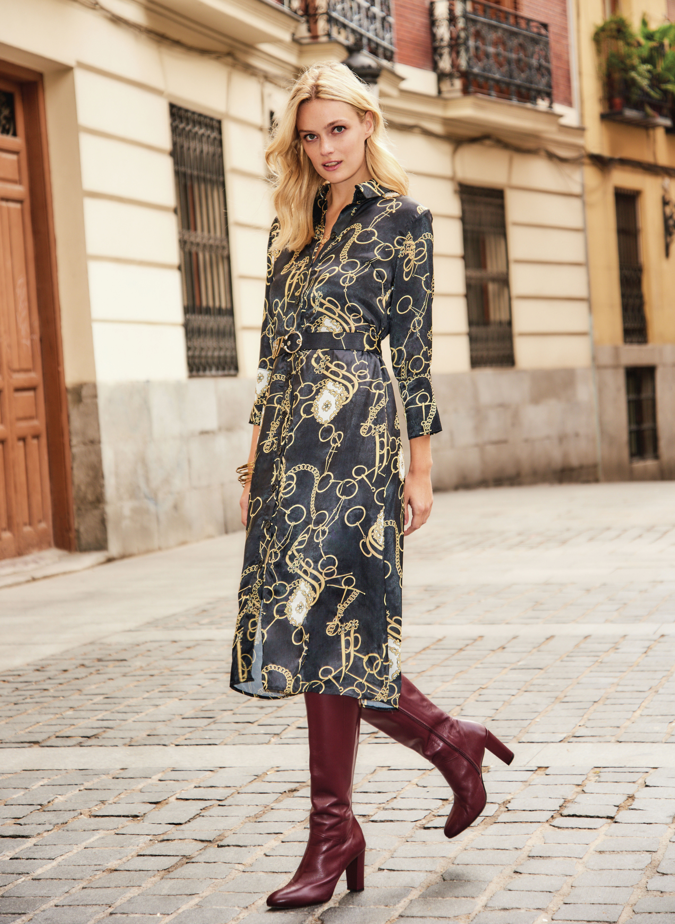 model wearing Sosandar Black Chain Print Shirt Dress With Belt; Burgundy Leather Zip Knee High Boots