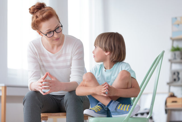Young female school psychologist having serious conversation with smart little boy at office