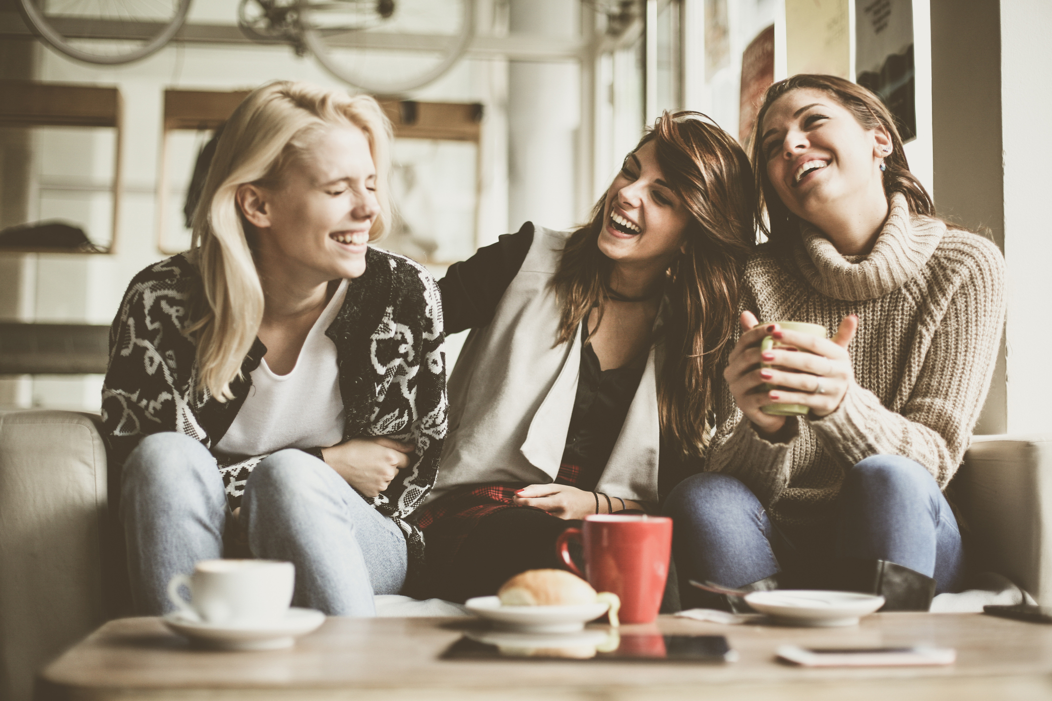 women chatting and laughing in a coffee shop