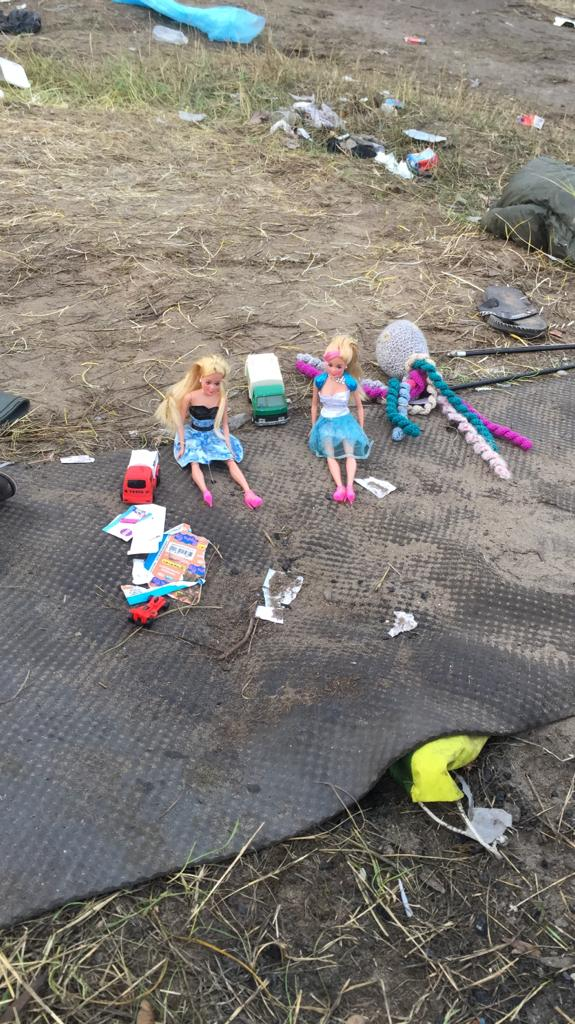 Dolls lie scattered on the muddy ground in Calais (PA)