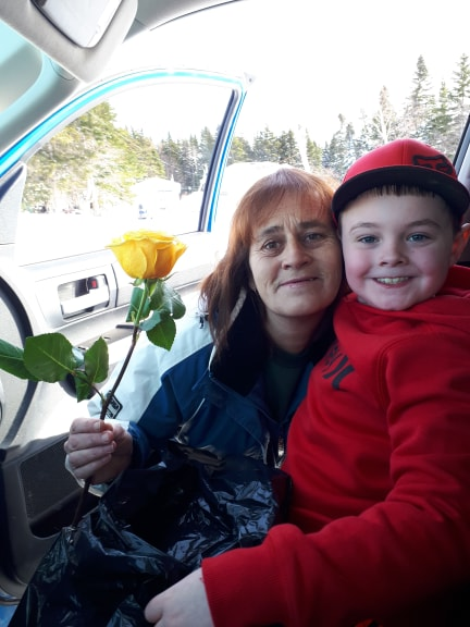Casey giving a rose to a women from his family's car