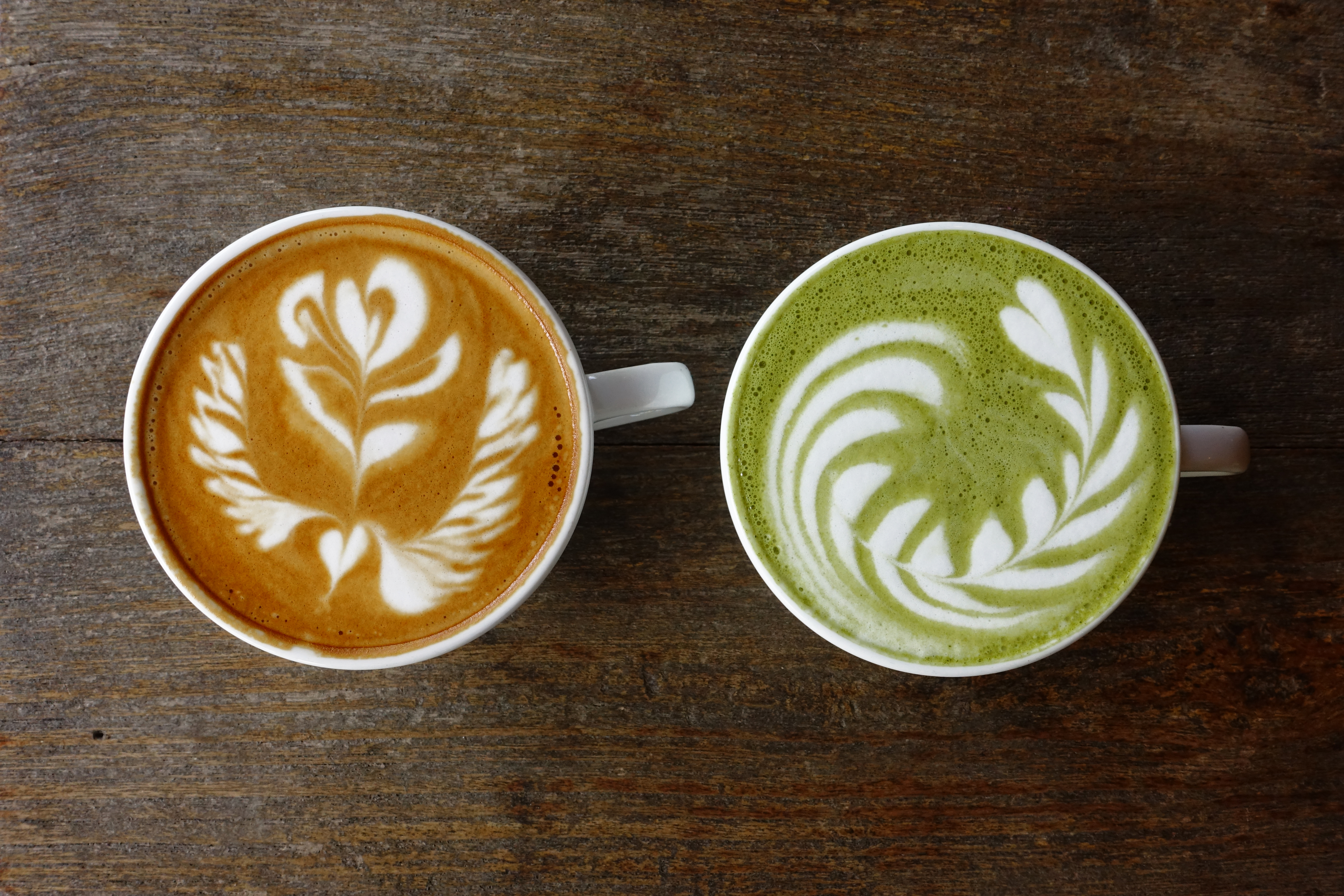 A cup of green tea matcha latte and cup of latte art coffee