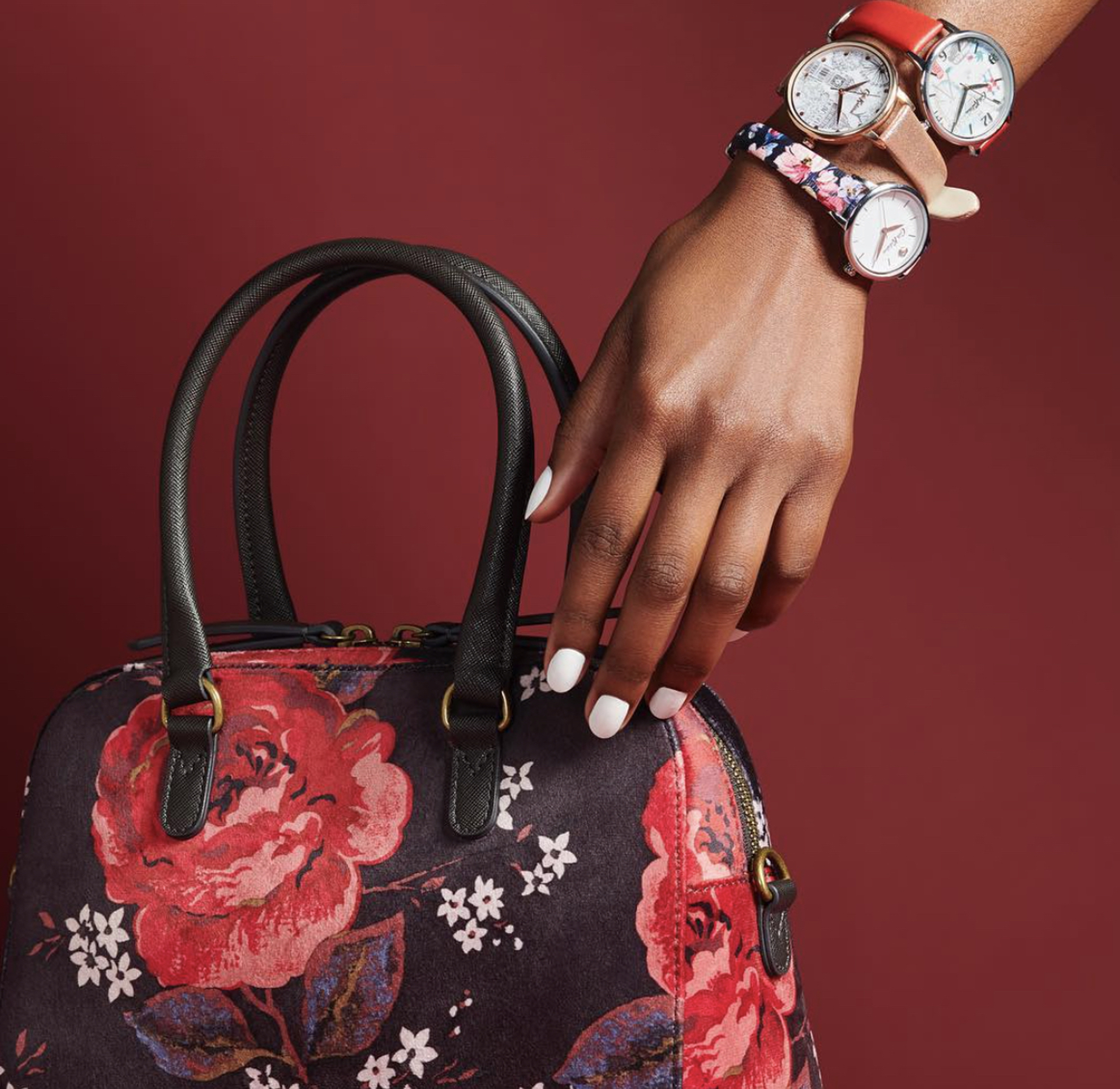 wrist with three Cath Kidston watches and a floral handbag