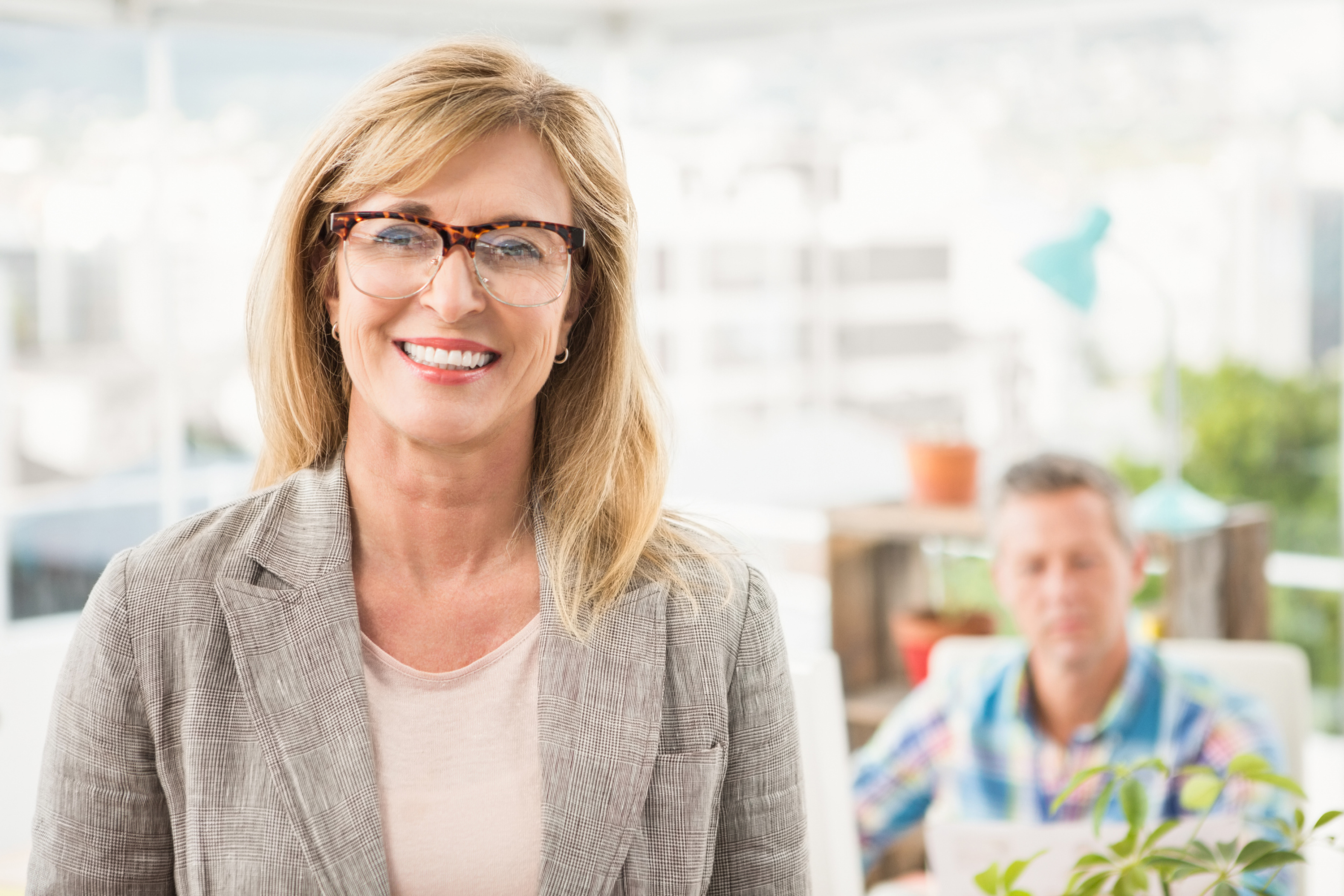Portrait of smiling casual businesswoman in front of her colleague in the office