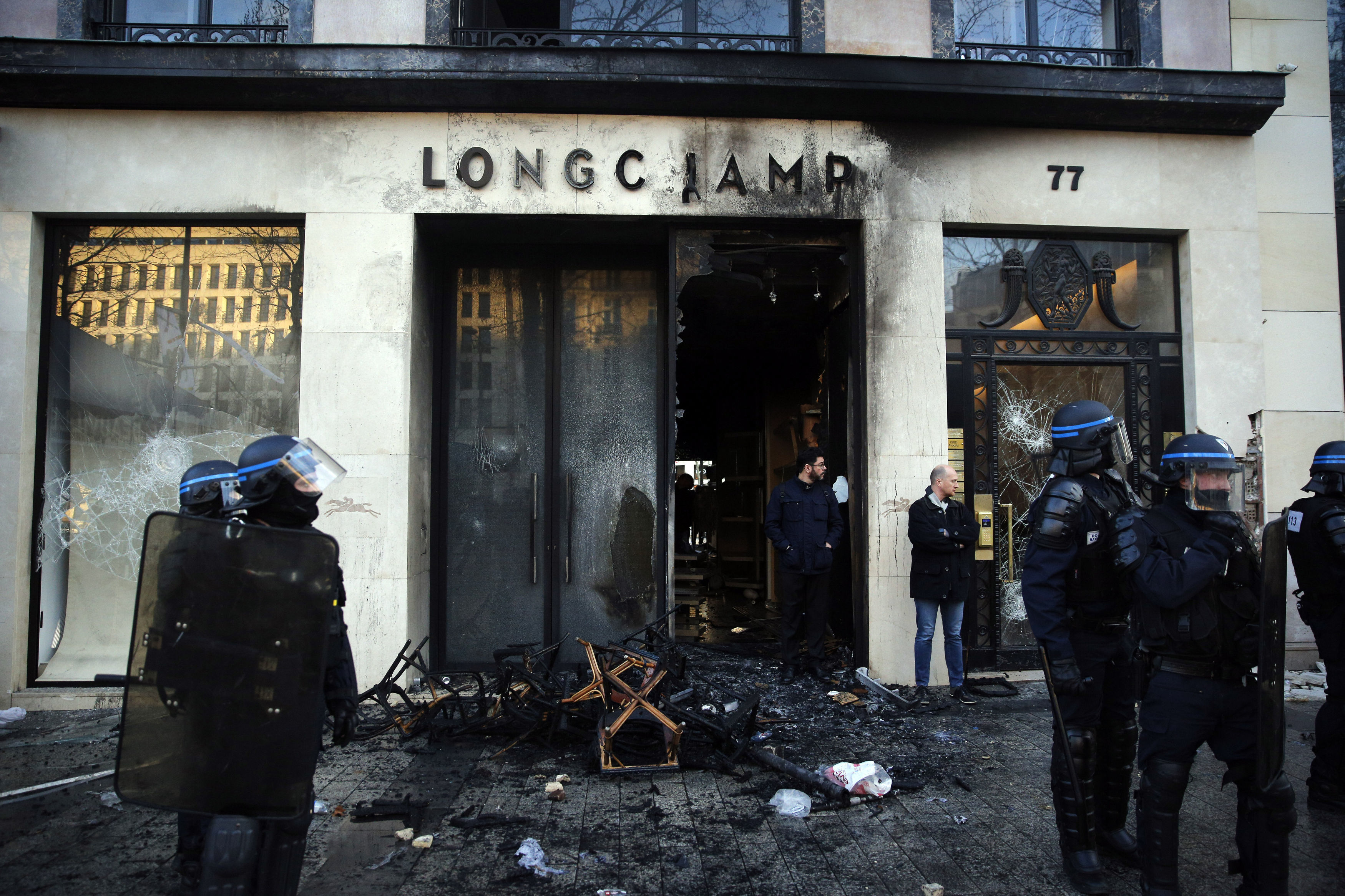 Riot police stand in front of a burned store