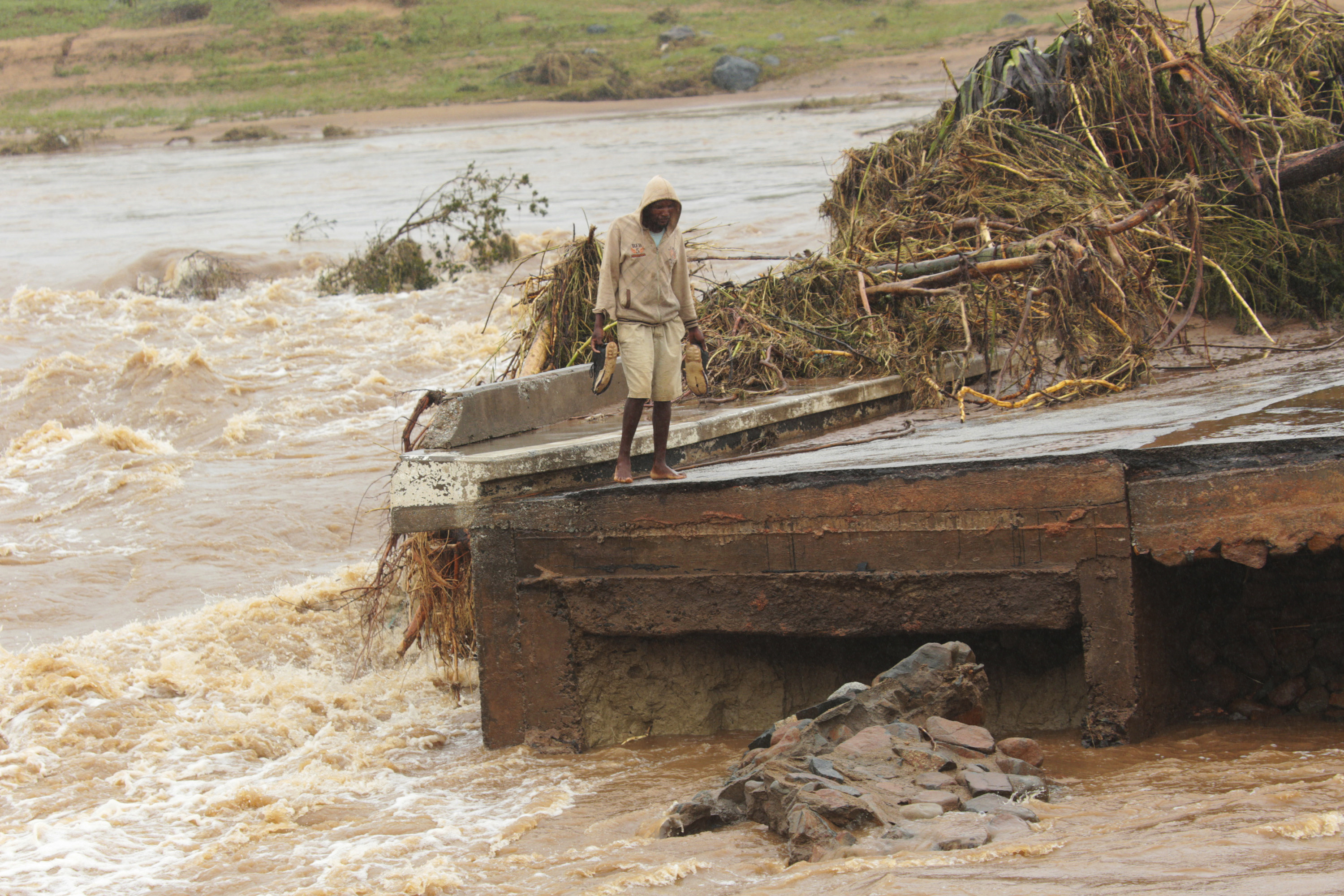 A man stands on the edge of a collapsed bridge in Chimanimani, about 600km south east of Harare, Zimbabwe