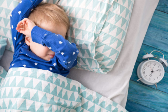 Young child covering his eyes in bed and trying to sleep