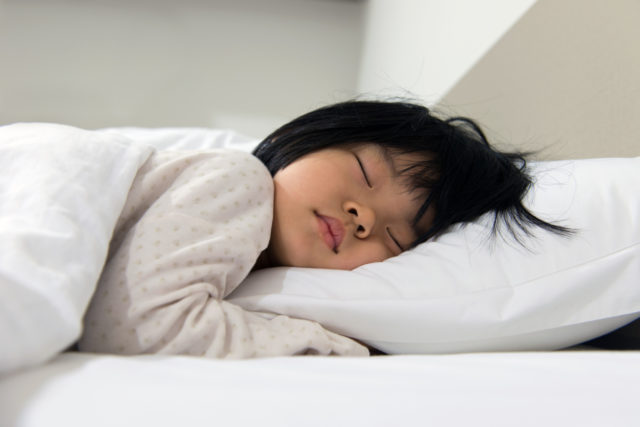 Child sleeping on her bed