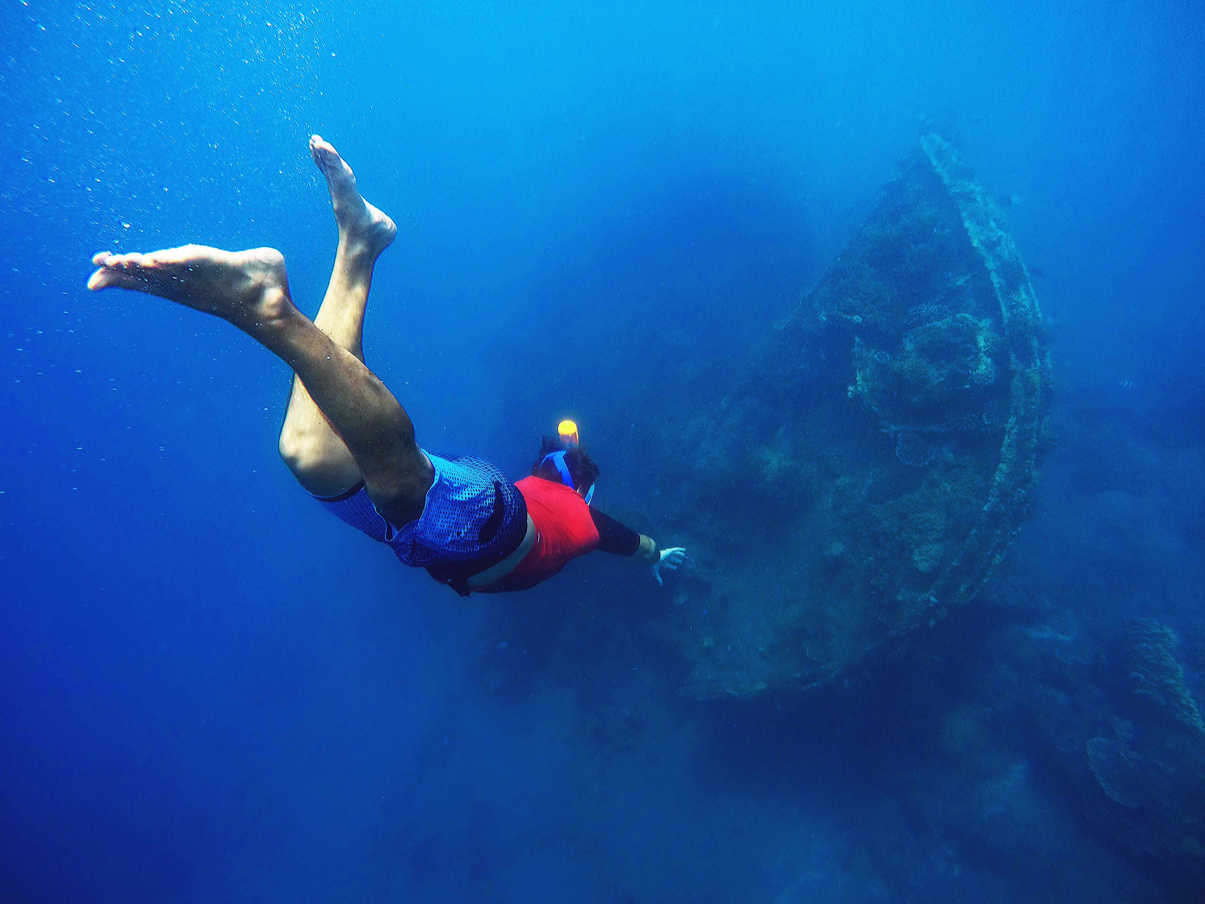 A freediver swimming down towards a wreck
