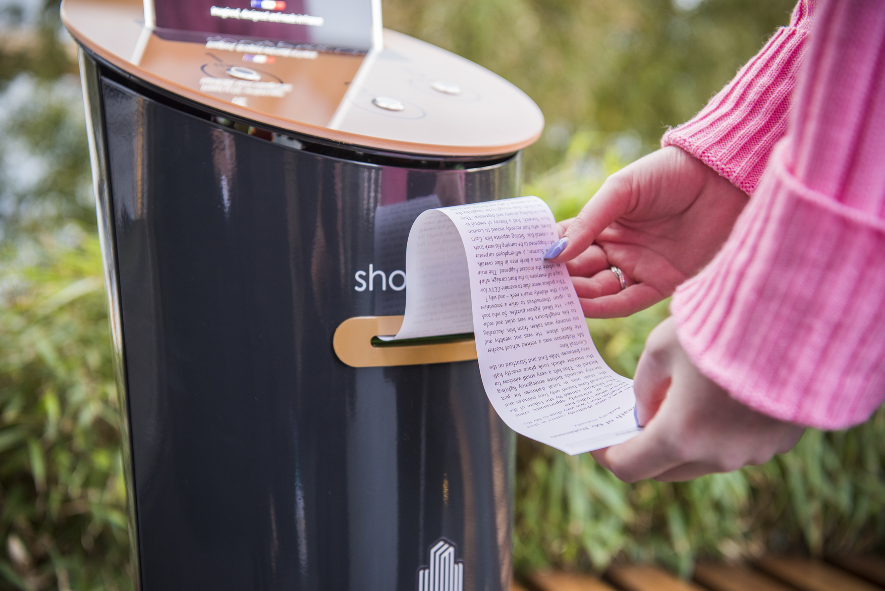 A woman uses a short story vending machine at Canary Wharf