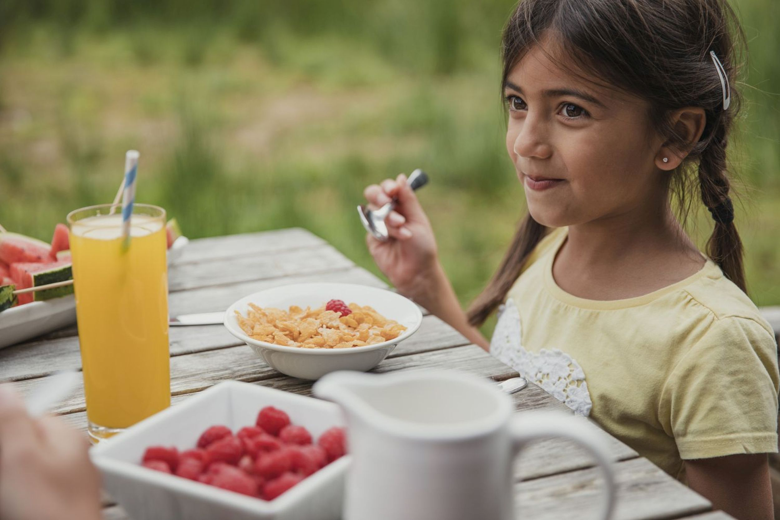 Little girl smiling as he eats her cereal outside (iStock/PA)