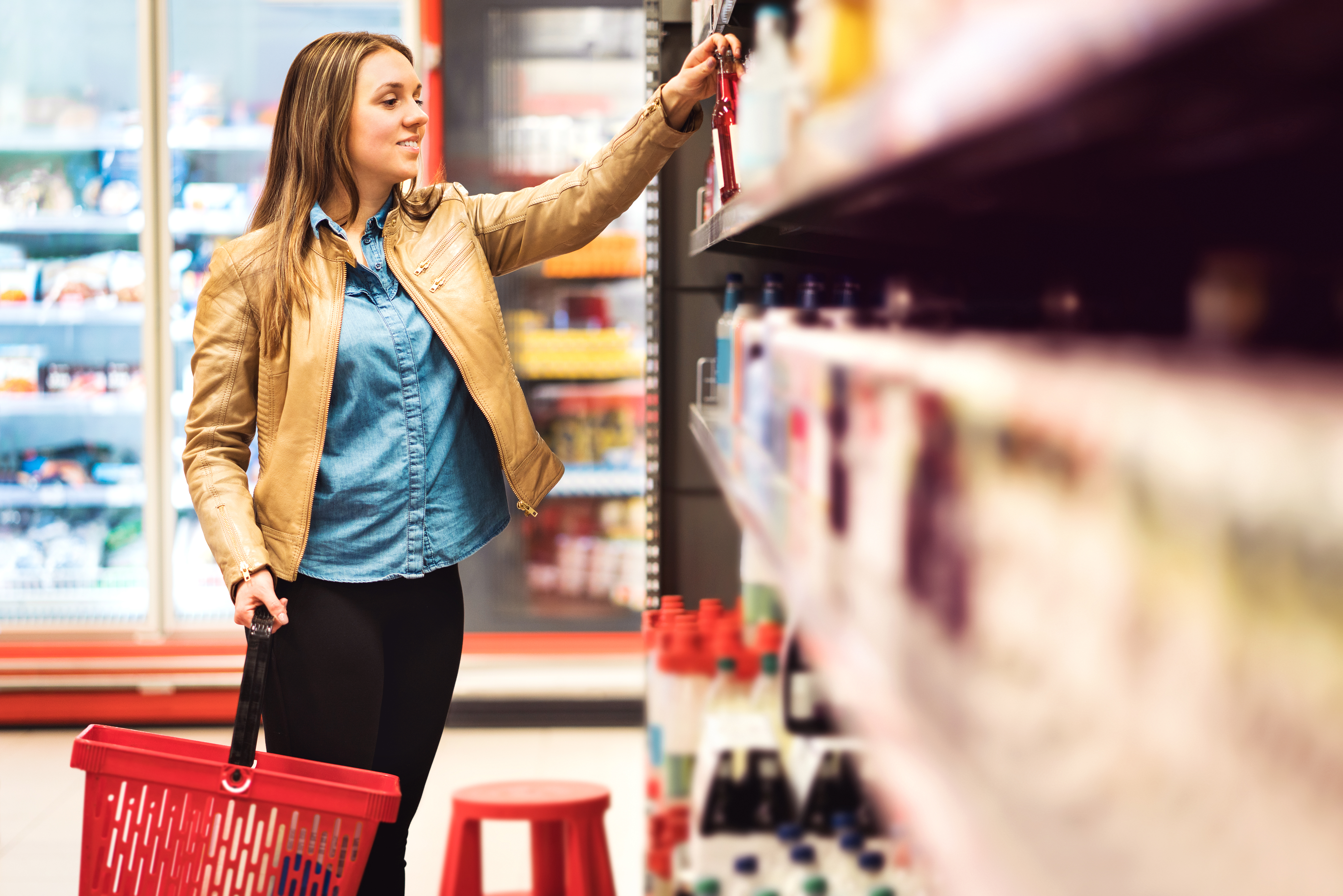 Customer in alcohol or drinks section in supermarket or liquor store holding a bottle from the shelf. Happy lady with shopping basket choosing alcoholic beverages.