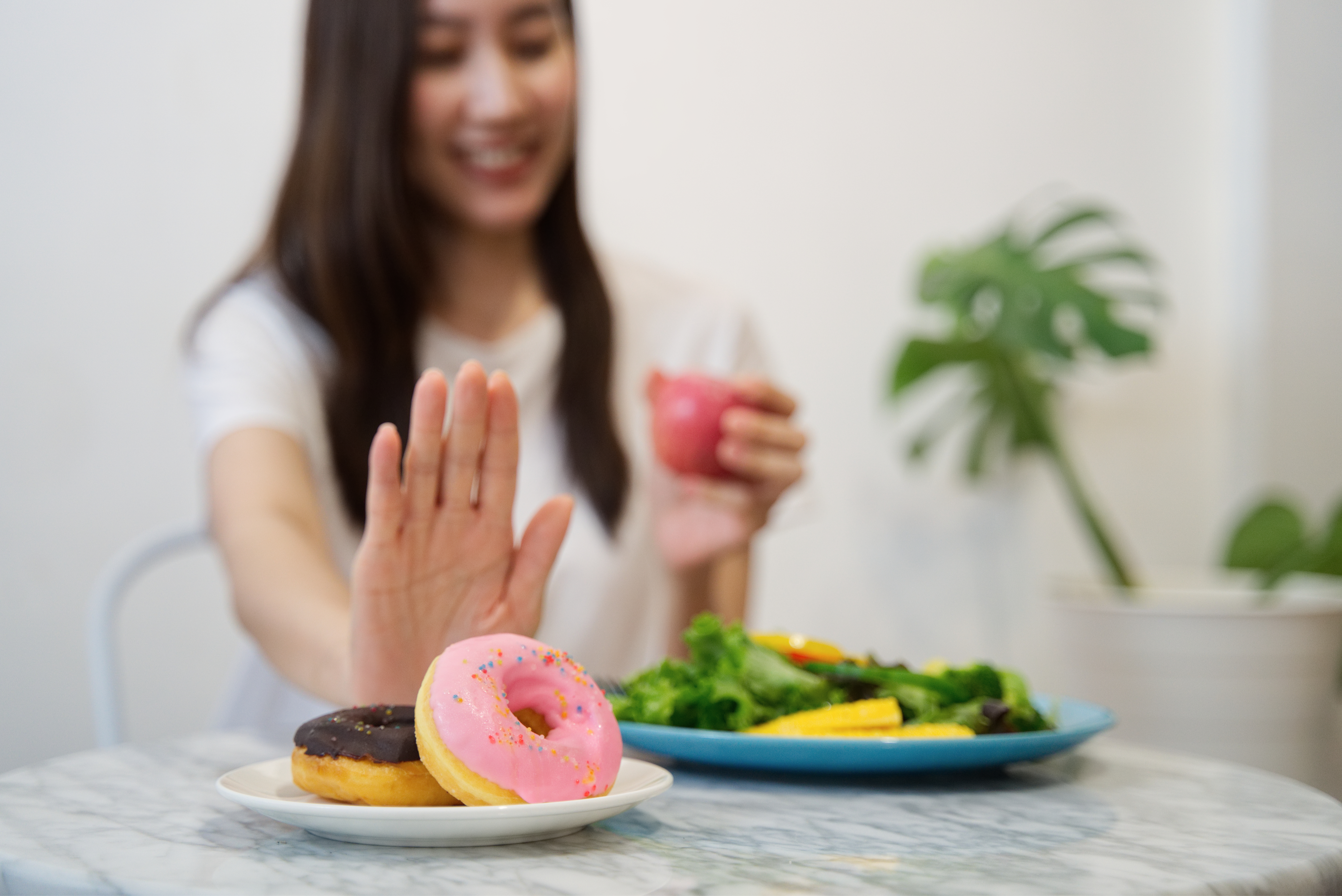 Young girl on dieting for good health concept. Close up female using hand reject junk food by pushing out her favorite donuts and choose red apple and salad for good health.
