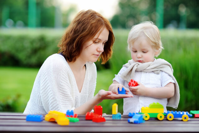 Young woman with his toddler son playing with colorful plastic blocks. Family leisure activity