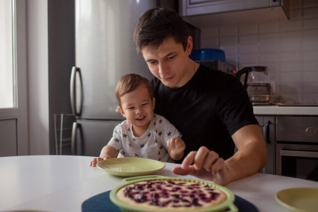 Father and son in the kitchen. kid wants a delicious hot cake. Young man with son, happy family