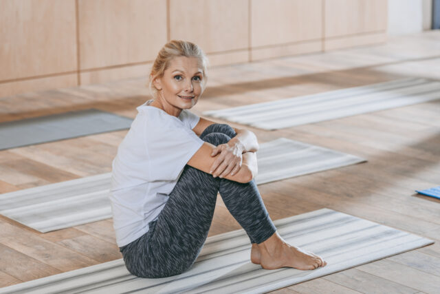 beautiful mature woman sitting on yoga mat and smiling at camera at training class