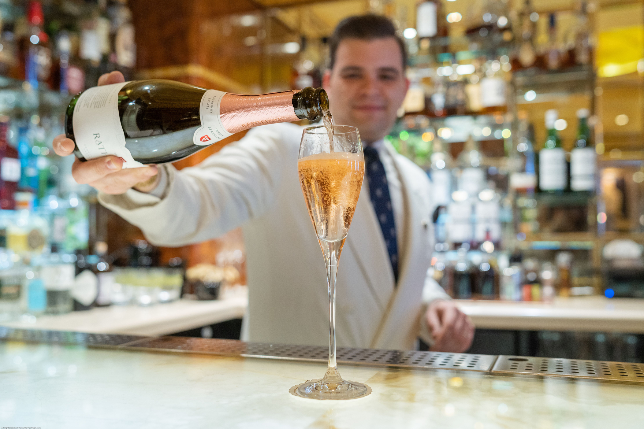Bartender at The Ritz pouring Rathfinny sparkling wine