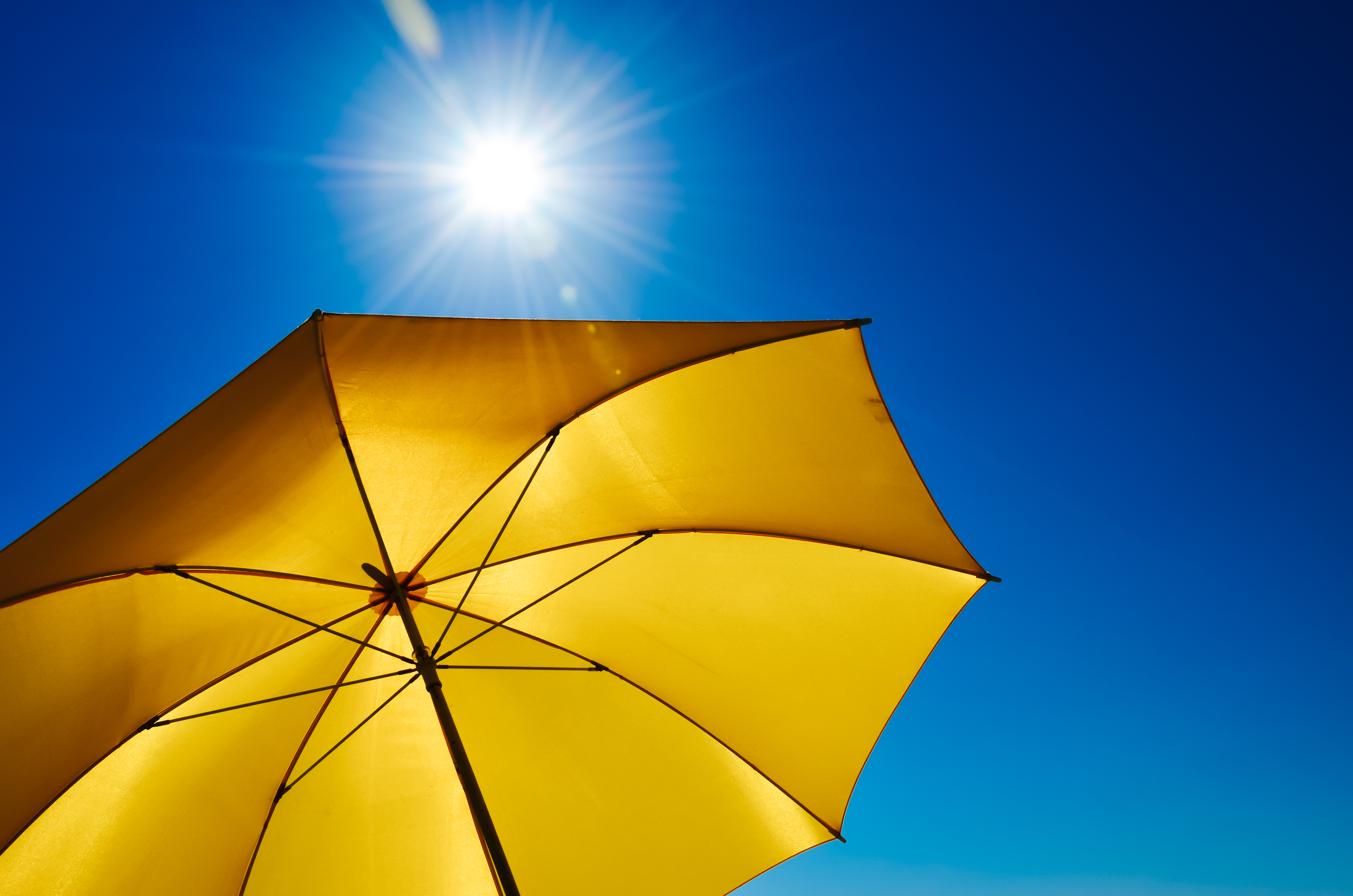 Yellow Umbrella With Bright Sun And Blue Sky